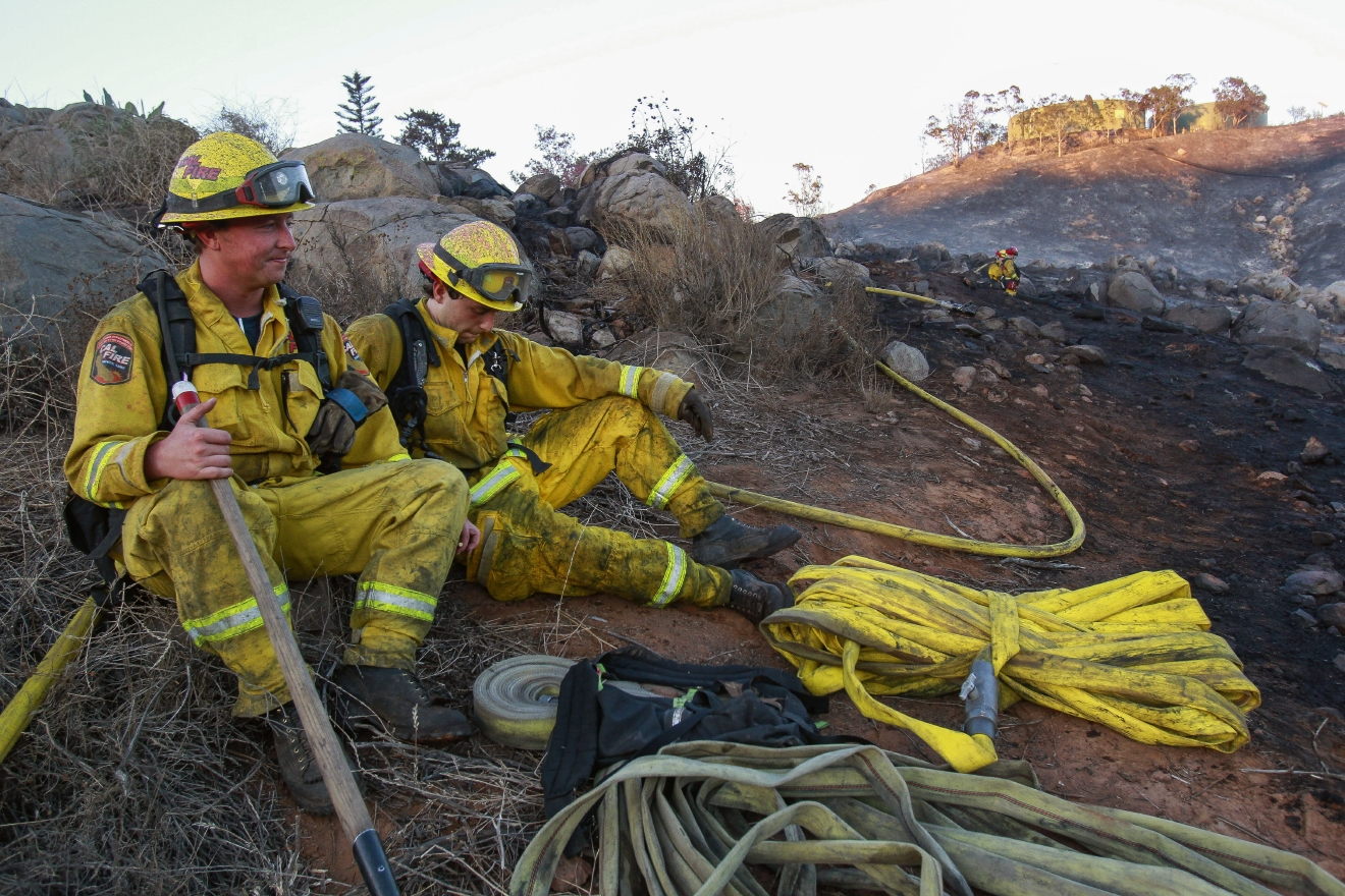 Cal Fire firefighters Josh Bates, left, and Justin Ware rest after fighting a wildfire in Spring Valley, Calif., Wednesday, Aug. 17, 2016. (Hayne Palmour IV/The San Diego Union-Tribune via AP)