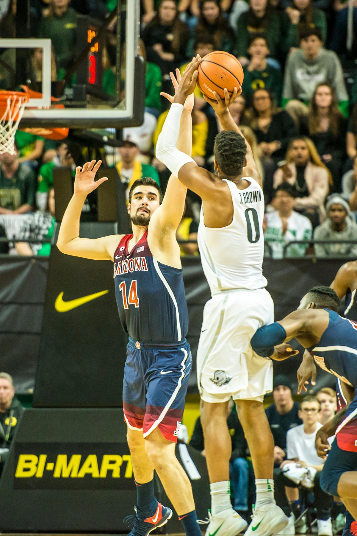 Oregon's Troy Brown (0) shoots over Arizona's Dusan Ristic (14) in their matchup at Matthew Knight Arena Sturday. The Ducks upset the fourteenth ranked Wildcats 98-93 in a stunning overtime win in front of a packed house of over 12,000 fans for their final home game to improve to a 19-10 (9-7 PAC-12) record on the season. Oregon will finish out regular season play on the road in Washington next week against Washington State on Thursday, then Washington on the following Saturday. (Photo by Colin Houck)