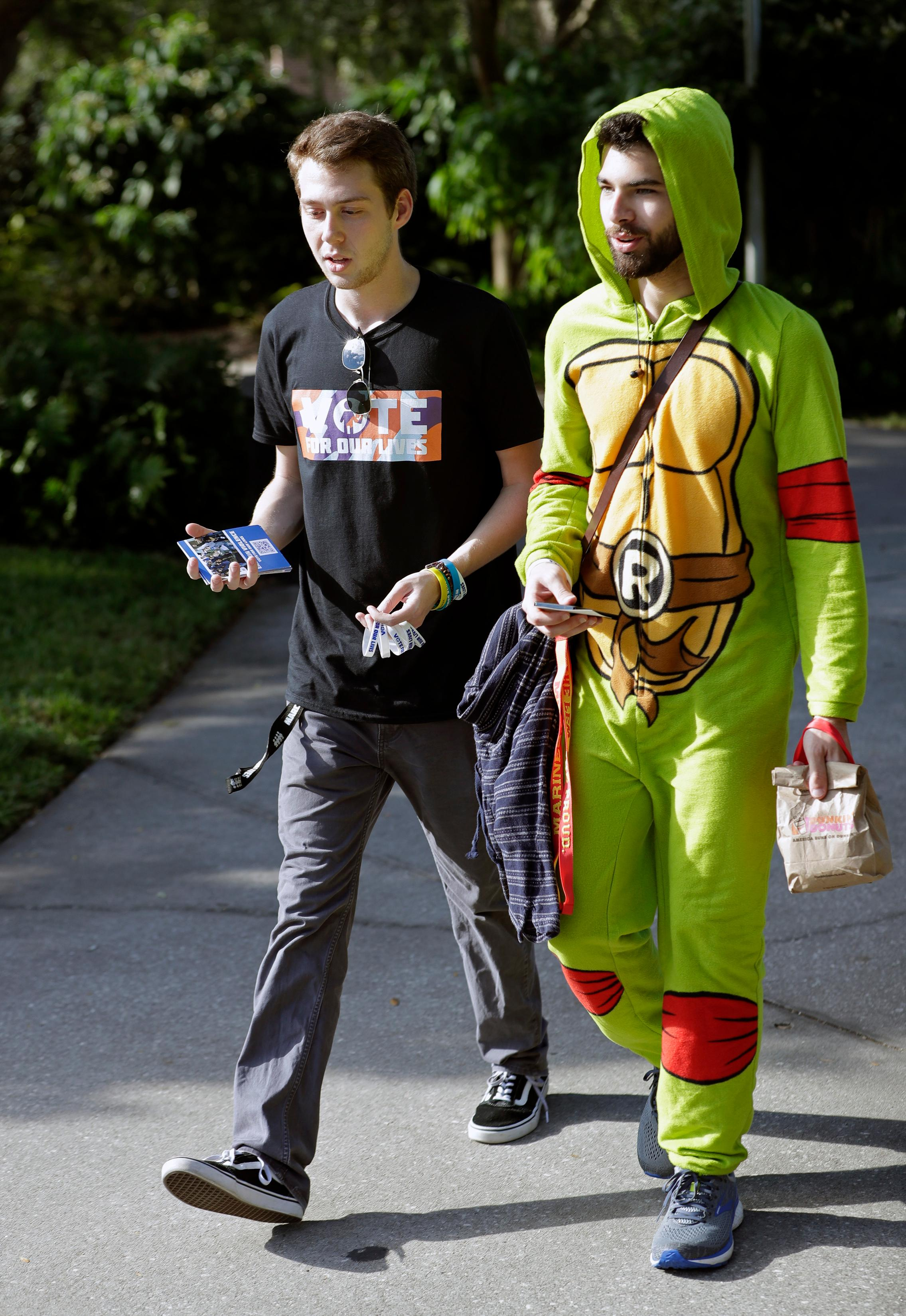In this Wednesday, Oct. 31, 2018 photo, Bradley Thornton, left, a student volunteer, escorts Gabriel Sanchez to a polling place on campus during a Vote for Our Lives event at the University of Central Florida in Orlando, Fla. (AP Photo/John Raoux)