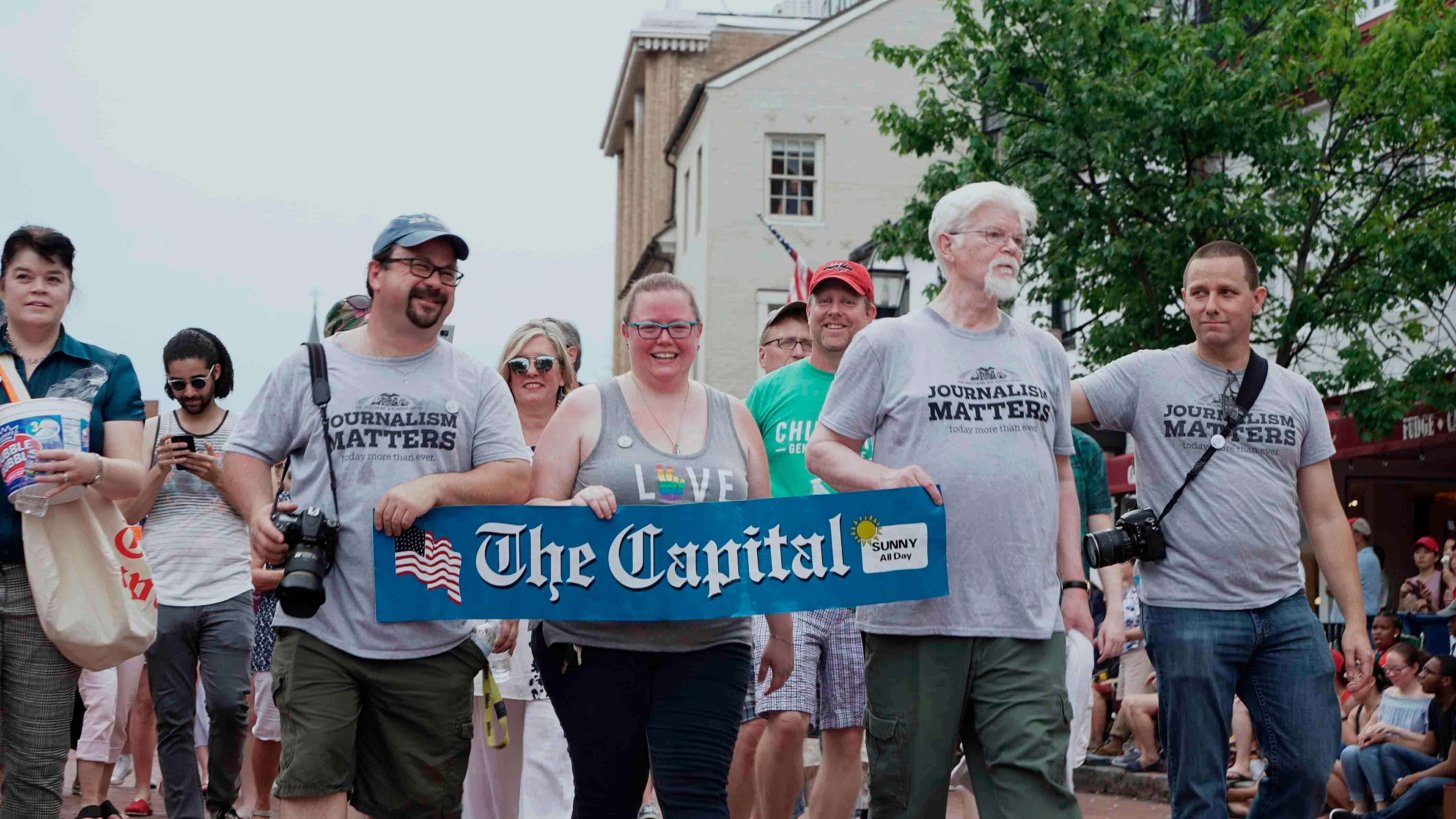 "Current and former Capital Gazette staff members march in the Annapolis 4th of July parade in Annapolis, Md., Wednesday, July 4, 2018. The Baltimore Sun reports that a few dozen current and former journalists from the Capital Gazette, where five employees were shot to death, participated in the Wednesday evening parade, where they were greeted by supportive whistles, cheers and applause. Several staffers T-shirts reading ""journalism matters,"" while others in the parade wore T-shirts that said, ""press on."" (Jay Reed/The Baltimore Sun via AP)"