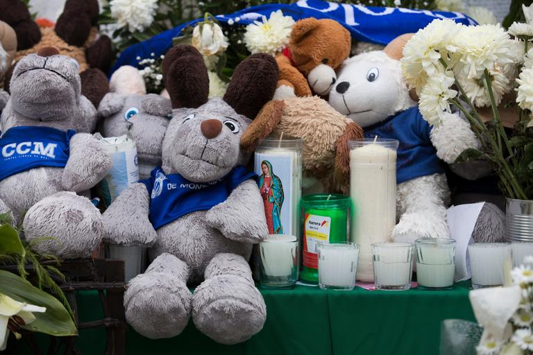 Stuffed ram plush toys, the college mascot of the Tecnologico de Monterrey, and candles, make up part of a memorial remembering five fellow students who died during the recent earthquake, in Mexico City, Thursday, Sept. 28, 2017. (AP Photo/Moises Castillo)