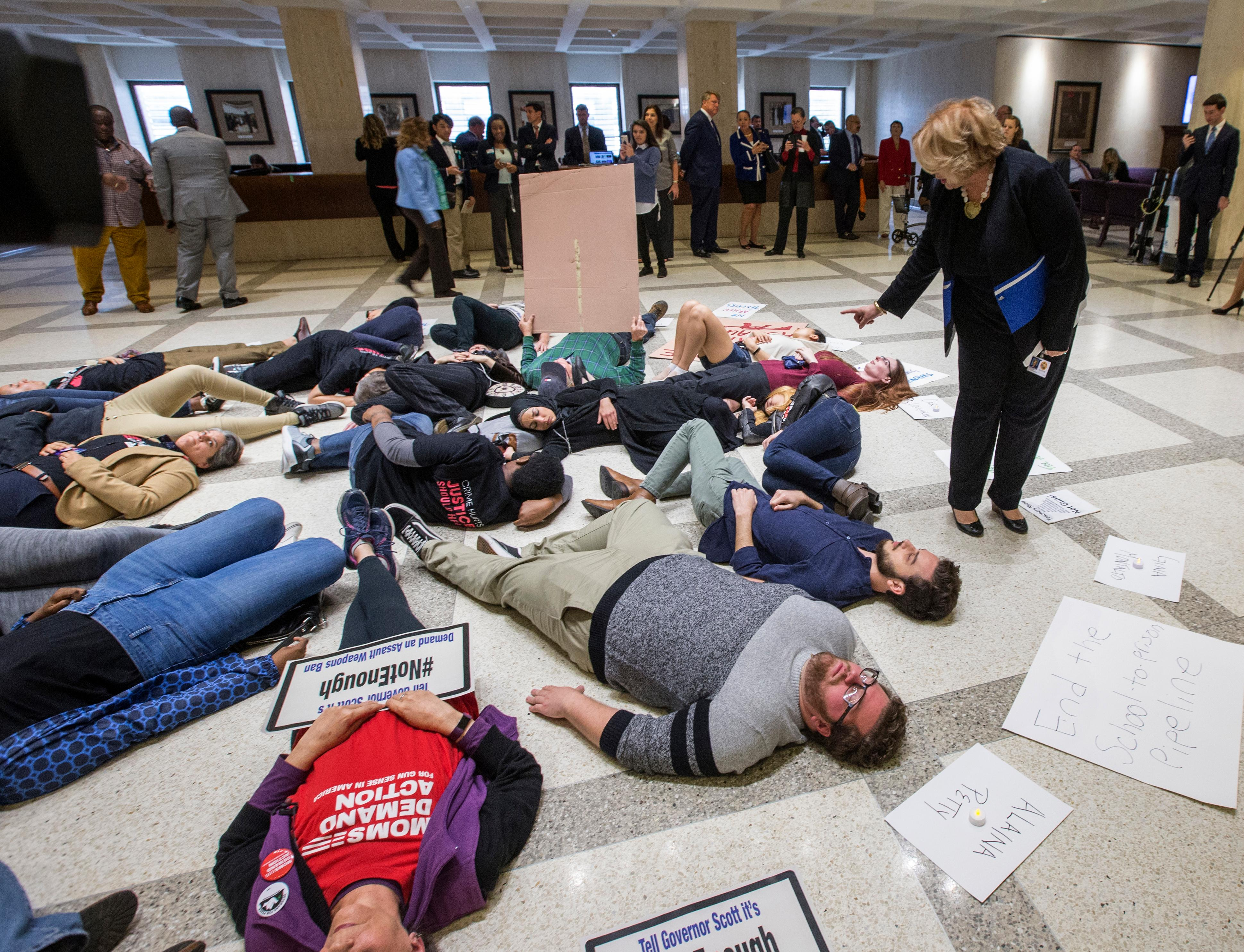 Florida Rep. Janet Cruz (D-Tampa) walks around a group of 20 college students and activists as they stage a die-in on the 4th floor rotunda between the House and Senate chambers while the House takes up the school safety bill at the Florida Capital in Tallahassee, Fla., Tuesday March 6, 2018. (AP Photo/Mark Wallheiser)