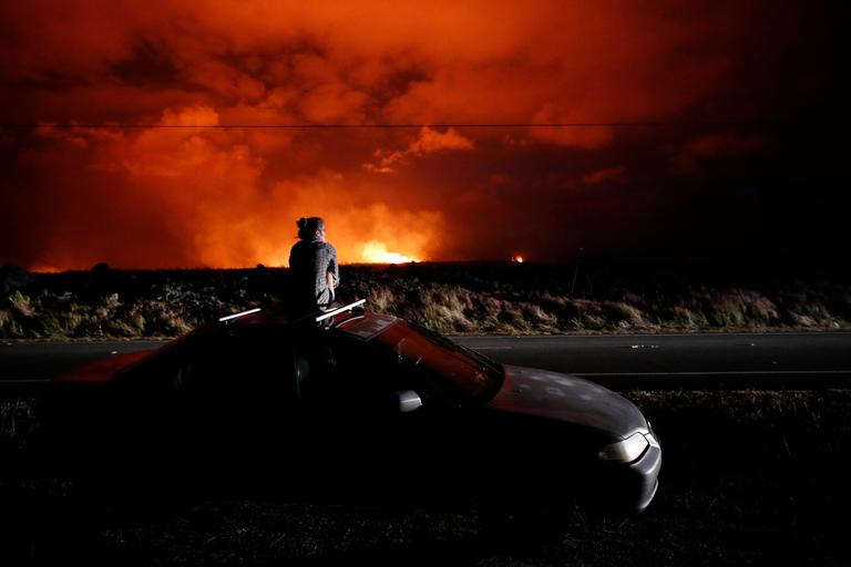 Brittany Kimball watches as lava erupts from from a fissure near Pahoa, Hawaii, Saturday, May 19, 2018. Two fissures that opened up in a rural Hawaii community have merged to produce faster and more fluid lava. Scientists say the characteristics of lava oozing from fissures in the ground has changed significantly as new magma mixes with decades-old stored lava. (AP Photo/Jae C. Hong)