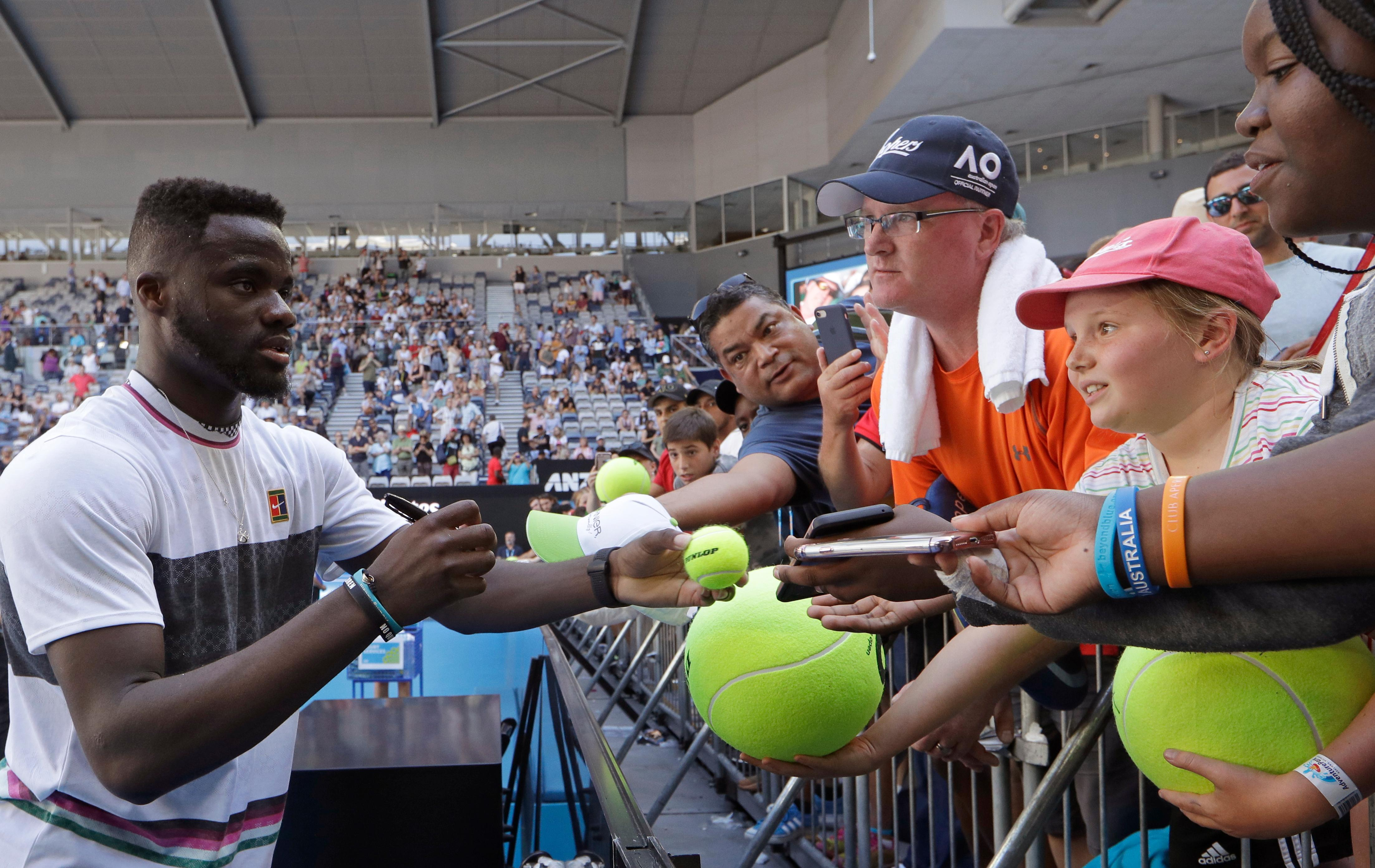 United States' Frances Tiafoe signs autographs after defeating Bulgaria's Grigor Dimitrov in their fourth round at the Australian Open tennis championships in Melbourne, Australia, Sunday, Jan. 20, 2019. (AP Photo/Kin Cheung)
