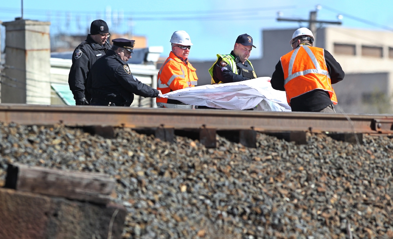 Police and investigators cover the body of one of the individuals killed in an Amtrak train crash in Chester, Pa., Sunday, April 3, 2016. The Amtrak train struck a piece of construction equipment just south of Philadelphia causing a derailment. (Michael Bryant/The Philadelphia Inquirer via AP)  PHIX OUT; TV OUT; MAGS OUT; NEWARK OUT; MANDATORY CREDIT