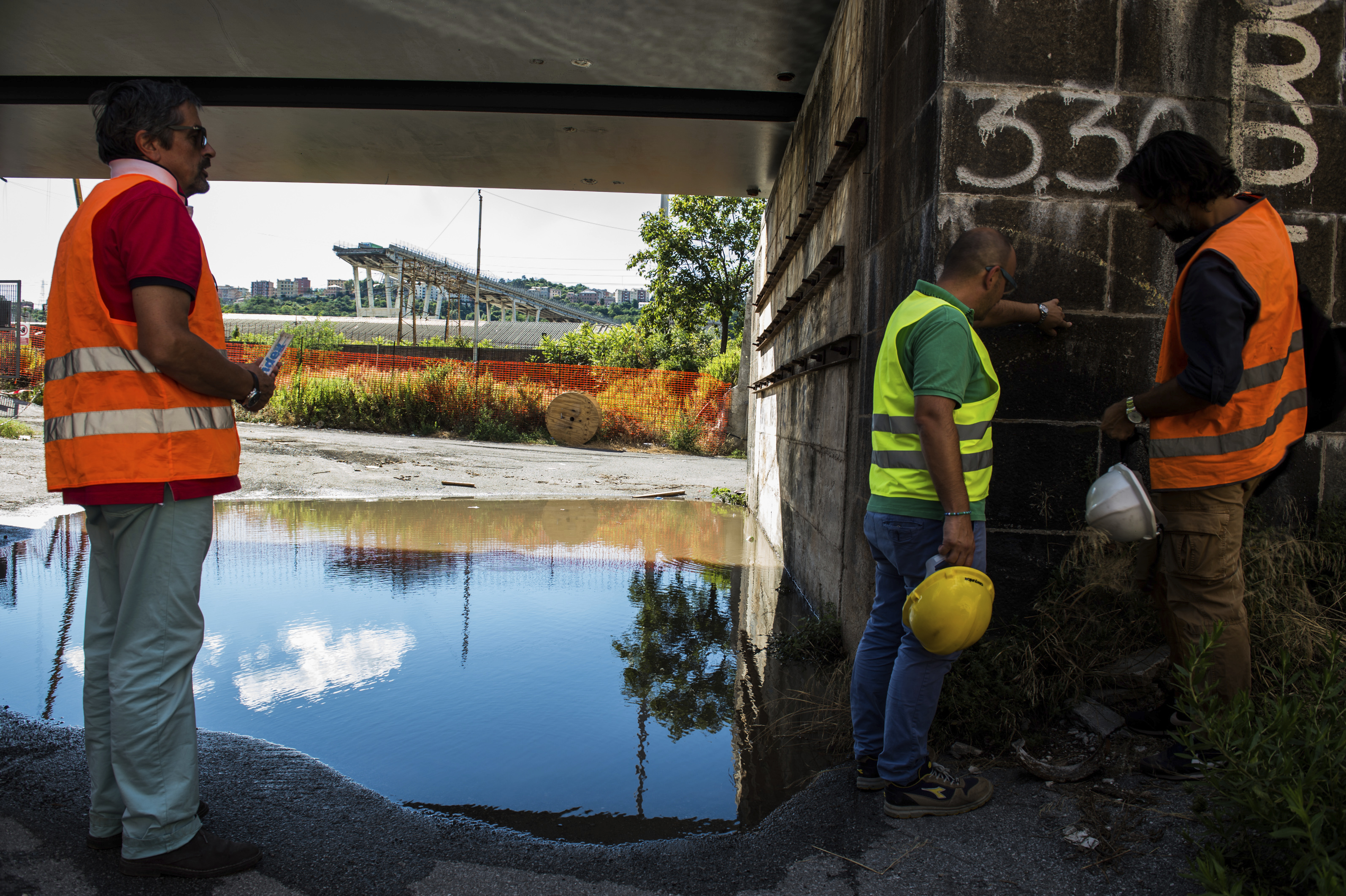 Workers inspect the the area around the collapsed Morandi highway bridge, in Genoa, northern Italy, Wednesday, Aug. 15, 2018. A bridge on a main highway linking Italy with France collapsed in the Italian port city of Genoa during a sudden, violent storm, sending vehicles plunging 90 meters (nearly 300 feet) into a heap of rubble below. (AP Photo/Nicola Marfisi)
