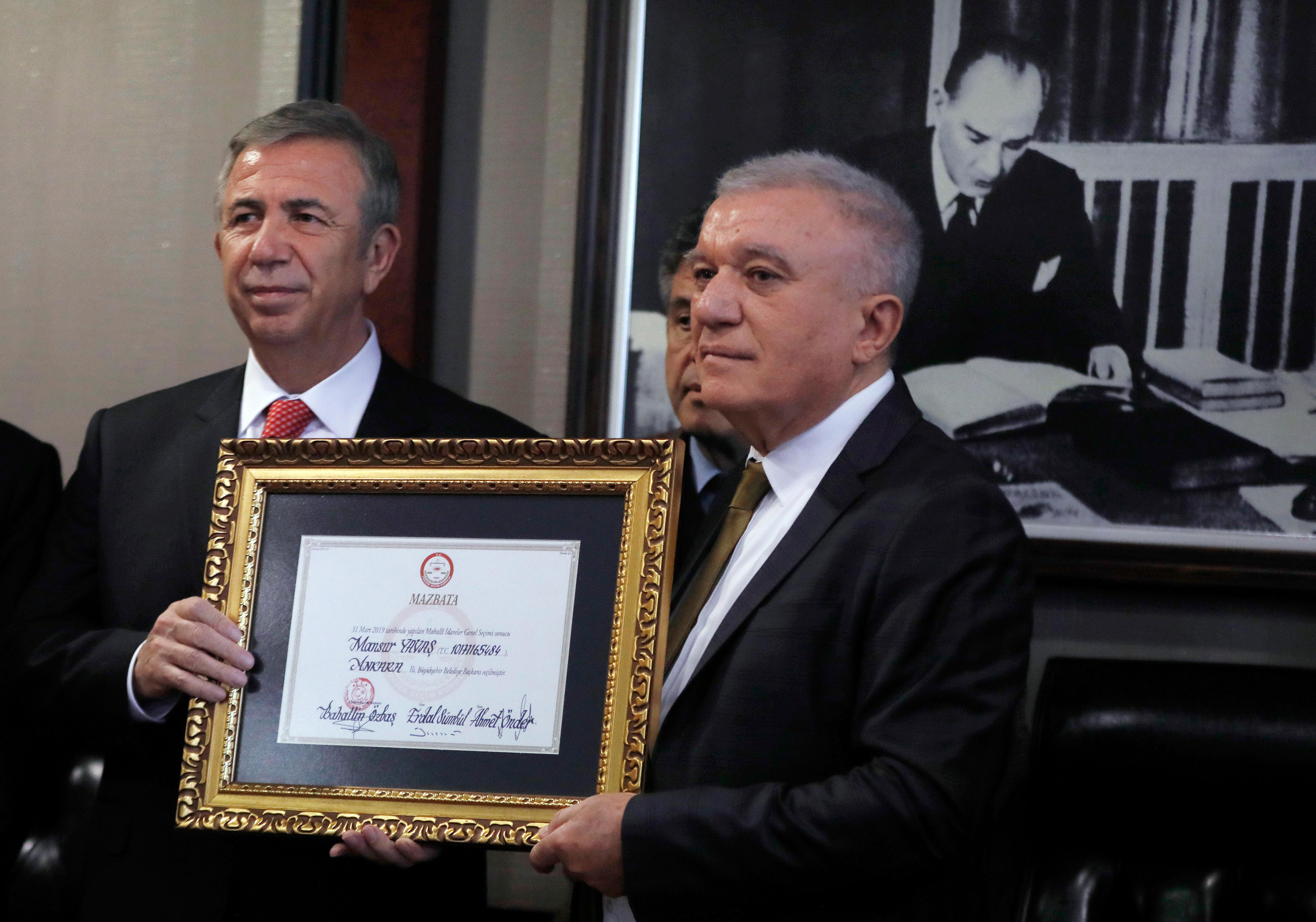 Mansur Yavas, the main Turkish opposition's candidate for the Turkish capital Ankara, left, receives the document from Bahattin Ozbas, the head of the election board, confirming him as the new mayor, in Ankara, Turkey, Monday April 8, 2019. (AP Photo/Burhan Ozbilici)