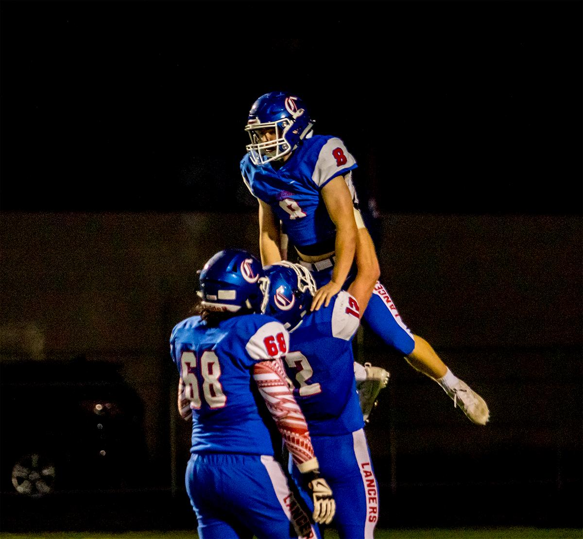 Churchill's Jax Arnold (#12) lifts up teammate Dalton McDaniel (#8) after a touchdown. Churchill defeated Crater 63-21 on Friday at their homecoming game. Churchill remains undefeated with a conference record of 9-0. Photo by August Frank, Oregon News Lab