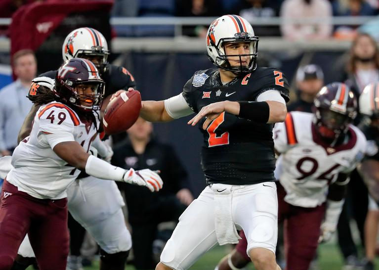 Oklahoma State quarterback Mason Rudolph (2) throws a pass as he is pressured by Virginia Tech linebacker Tremaine Edmunds (49) and defensive end Trevon Hill (94) during the first half of the Camping World Bowl NCAA college football game Thursday, Dec. 28, 2017, in Orlando, Fla. (AP Photo/John Raoux)