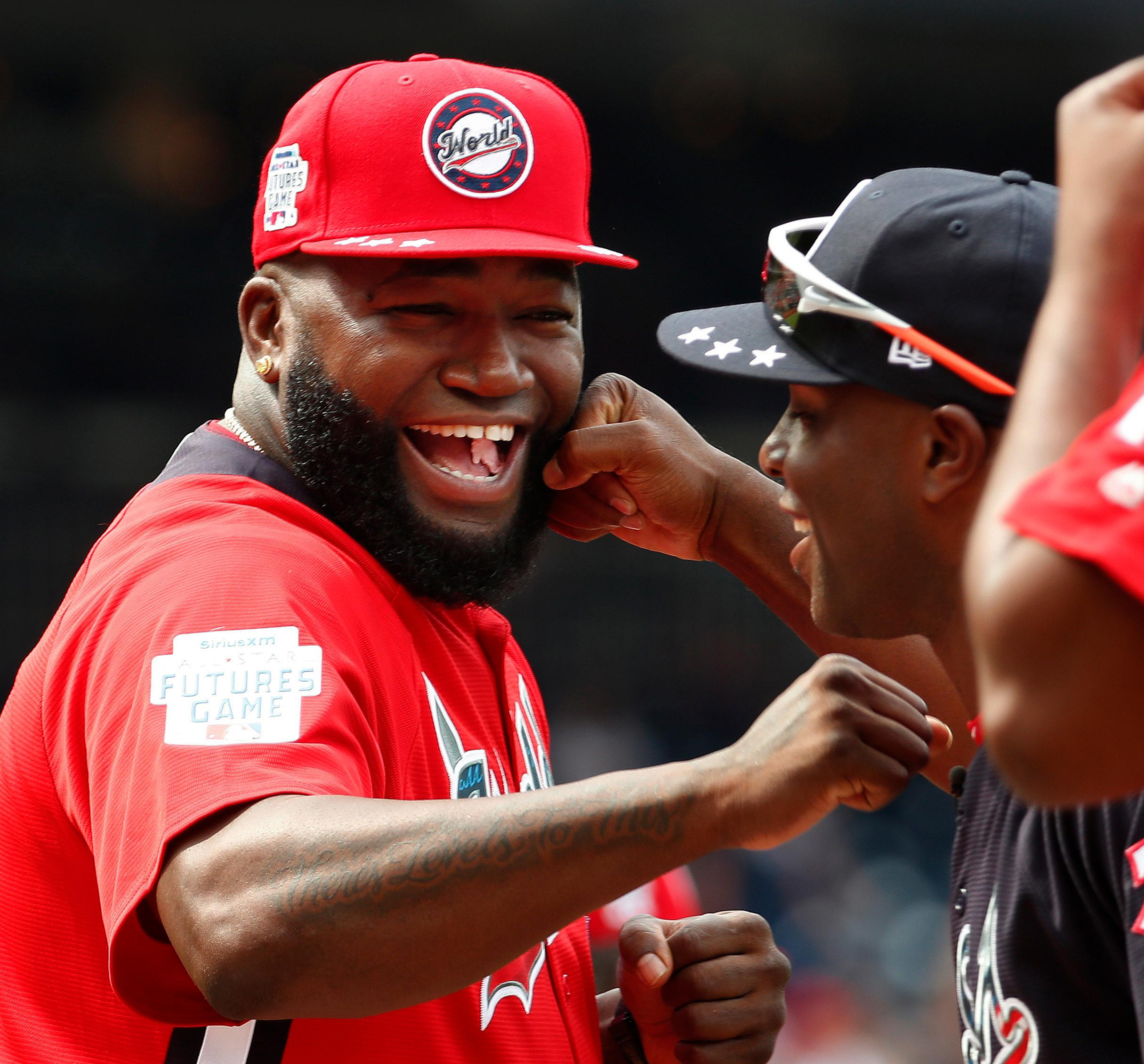 FILE - In this July 15, 2018, file photo, World Team Manager David Ortiz (34) speaks with U.S. Team Manager Torrii Hunter, before the All-Star Futures baseball game at Nationals Park, in Washington. Ortiz returned to Boston for medical care after being shot in a bar Sunday, June 9, 2019, in his native Dominican Republic. (AP Photo/Alex Brandon, File)