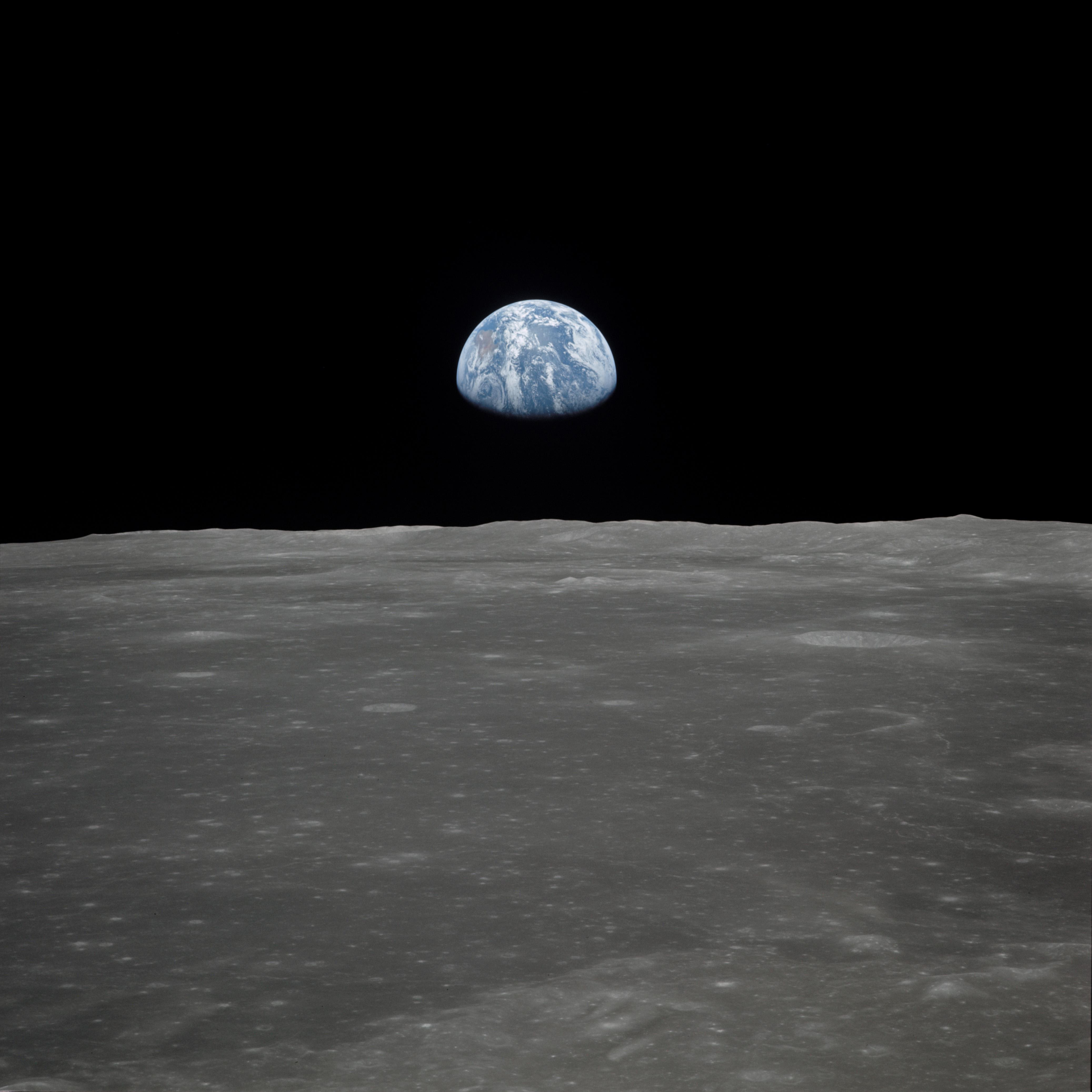 "This view of Earth rising over the Moon's horizon was taken from the Apollo 11 spacecraft. The lunar terrain pictured is in the area of Smyth's Sea on the nearside. Coordinates of the center of the terrain are 85 degrees east longitude and 3 degrees north latitude. While astronaut Neil A. Armstrong, commander; and Edwin E. Aldrin Jr., lunar module pilot, descended in the Lunar Module (LM) ""Eagle"" to explore the Sea of Tranquility region of the moon, astronaut Michael Collins remained with the Command and Service Modules (CSM) ""Columbia"" in lunar orbit. (Photo: NASA)"