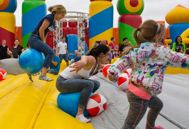 Measuring in at 10,000 square feet and 32 feet tall, the worlds largest bouncy castle ever created stops at Kelley Farms this weekend in Bonney Lake. Families walked through the doors of the inflatable castle and tested their skills on the obstacle course, while listening to tunes played by a live DJ. (Sy Bean / Seattle Refined)