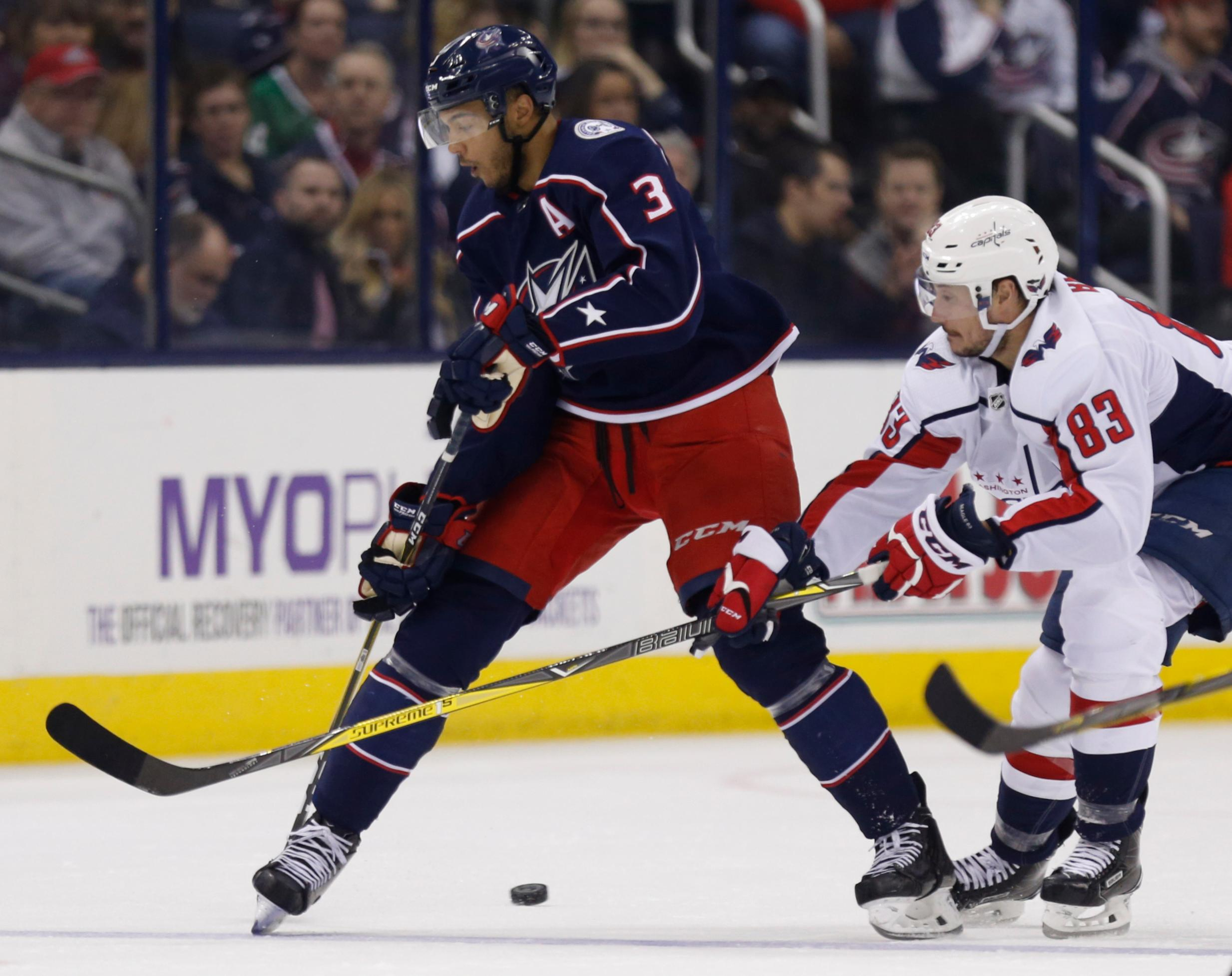 Columbus Blue Jackets defenseman Seth Jones, left, passes the puck against Washington Capitals forward Jay Beagle during the second period of an NHL hockey game in Columbus, Ohio, Monday, Feb. 26, 2018. (AP Photo/Paul Vernon)