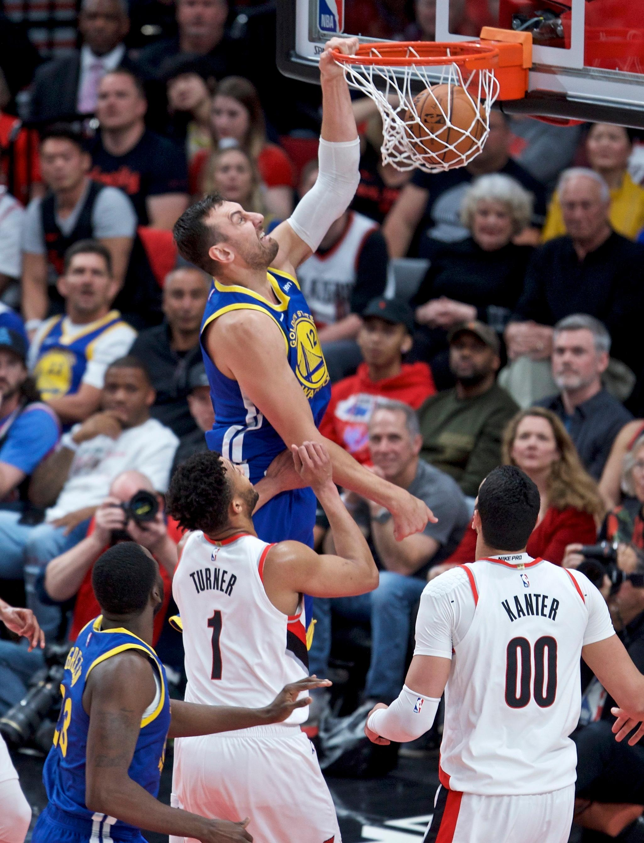 Golden State Warriors center Andrew Bogut, top, dunks over Portland Trail Blazers guard Evan Turner during the first half of Game 4 of the NBA basketball playoffs Western Conference finals Monday, May 20, 2019, in Portland, Ore. (AP Photo/Craig Mitchelldyer)