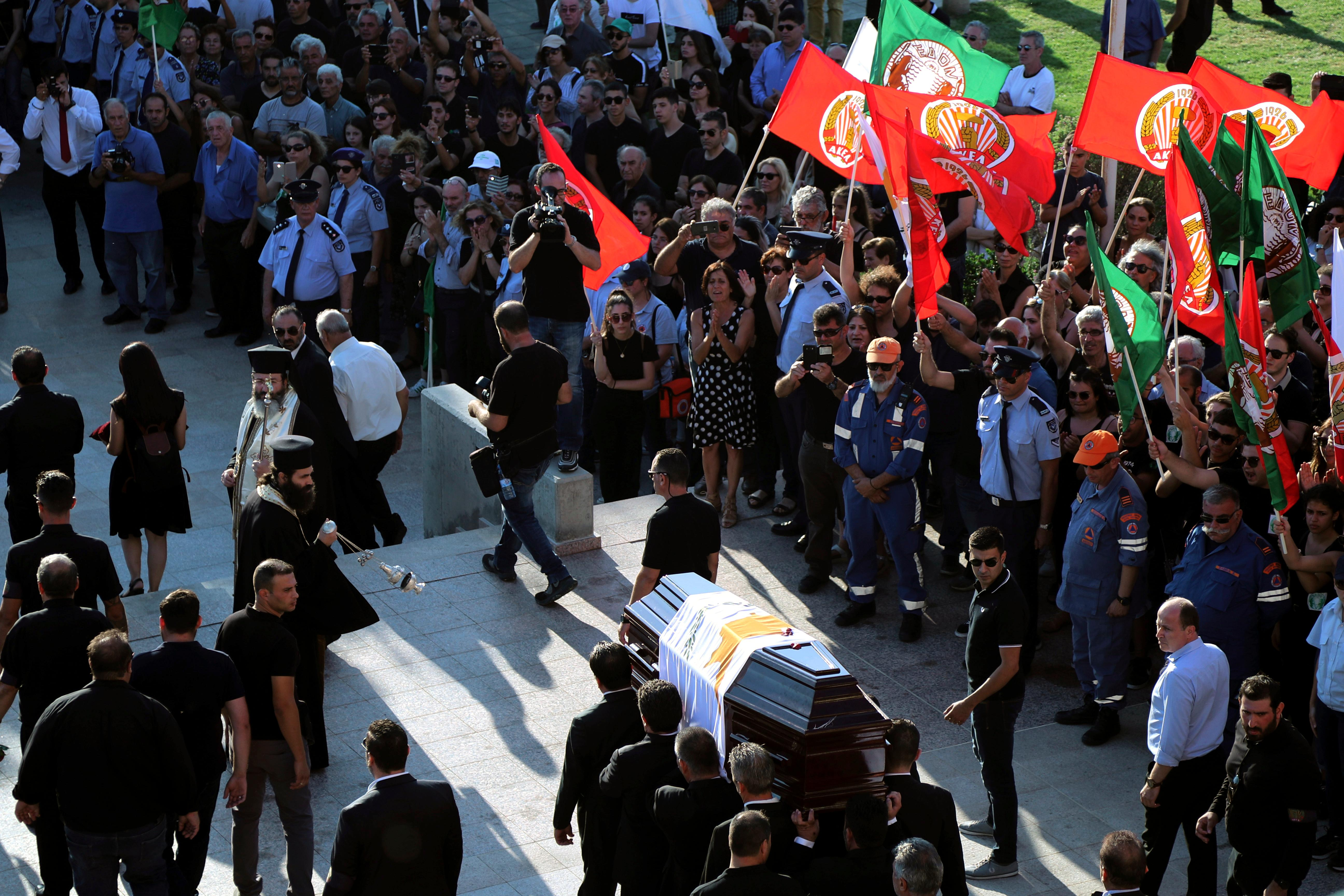 Pallbearers carry the coffin of the former Cyprus' President Dimitris Christofias, as people wave flags of communist party (AKEL) during his state funeral at the Orthodox Christian Church of the Lord's Wisdom in capital Nicosia, Cyprus, Tuesday, June 25, 2019. (AP Photo/Petros Karadjias)
