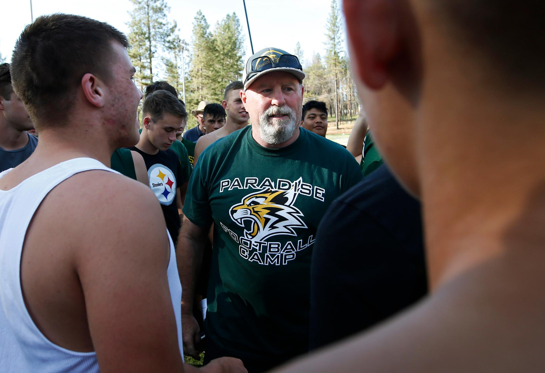 In this Thursday, Aug. 22, 2019, photo, Rick Prinz, center, coach of the Paradise High School football team, meets with his players after practice in Paradise, Calif.{ } (AP Photo/Rich Pedroncelli)
