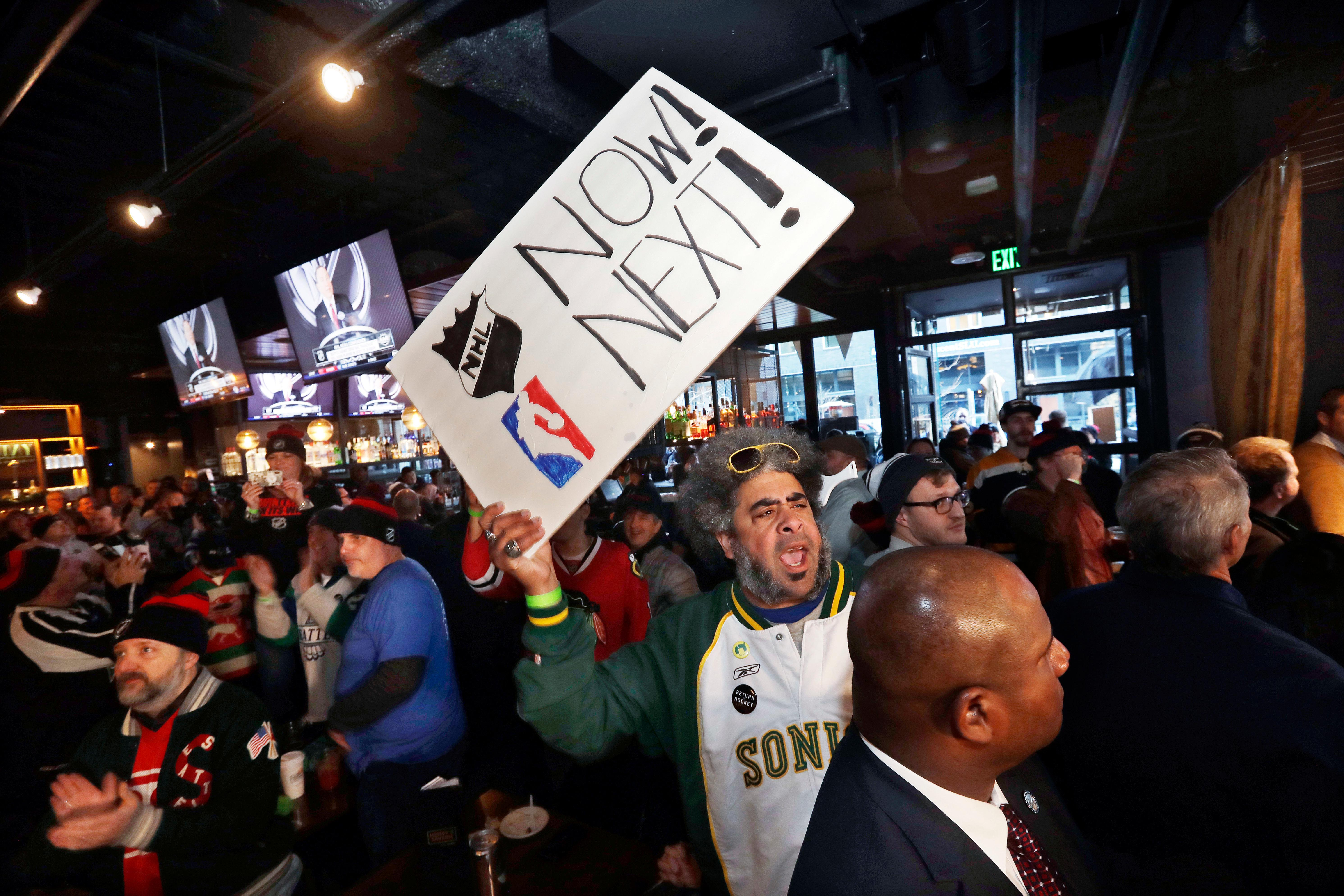 "Kris ""Sonic Guy"" Brannon holds up a sign in support of adding an NBA team following the announcement of a new NHL hockey team in Seattle, at a celebratory party Tuesday, Dec. 4, 2018, in Seattle.  (AP Photo/Elaine Thompson)"