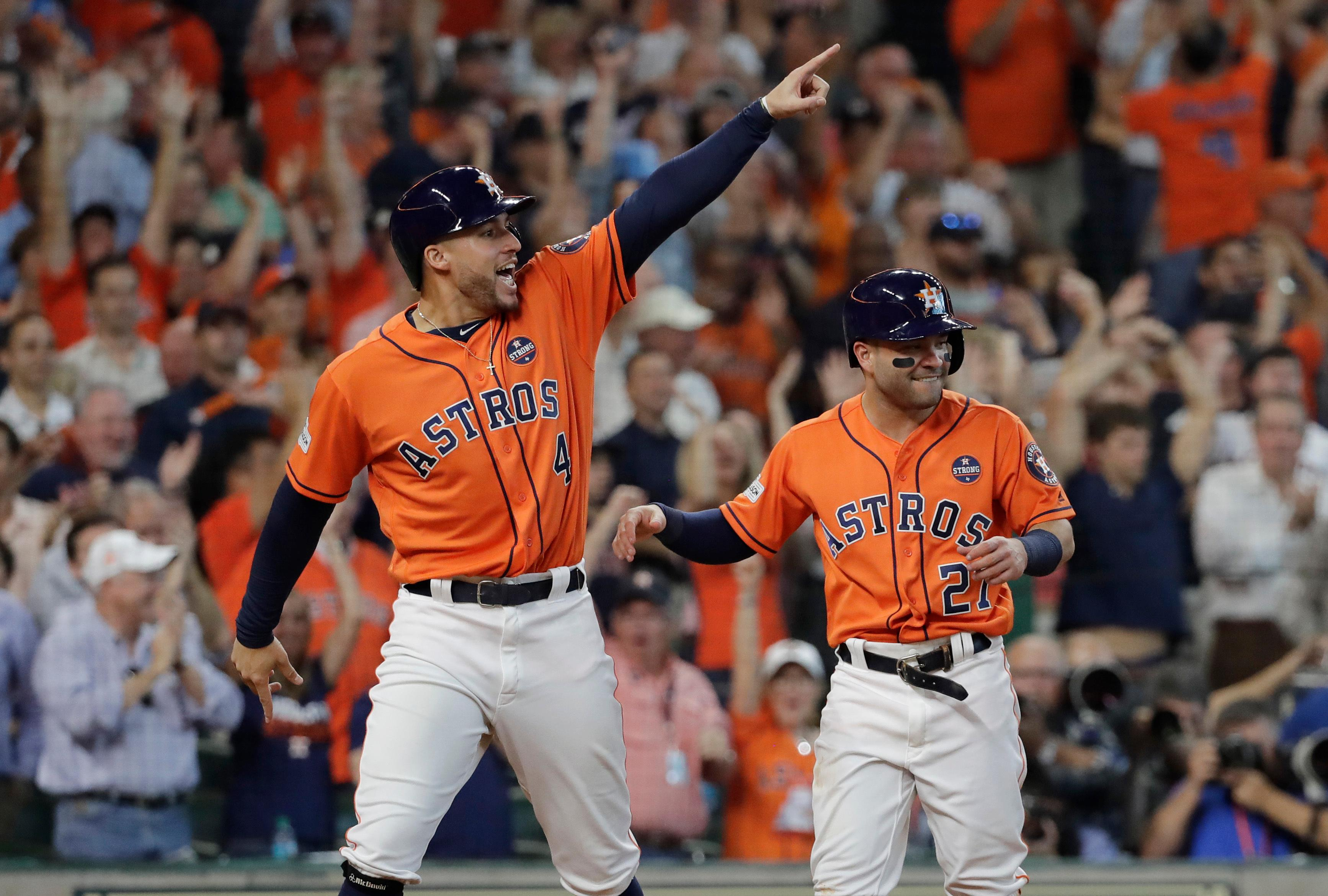 Houston Astros' George Springer (4) and Jose Altuve (27) celebrate after they scored on teammate Carlos Correa's double in Game 2 of baseball's American League Division Series against the Boston Red Sox, Friday, Oct. 6, 2017, in Houston. (AP Photo/David J. Phillip)