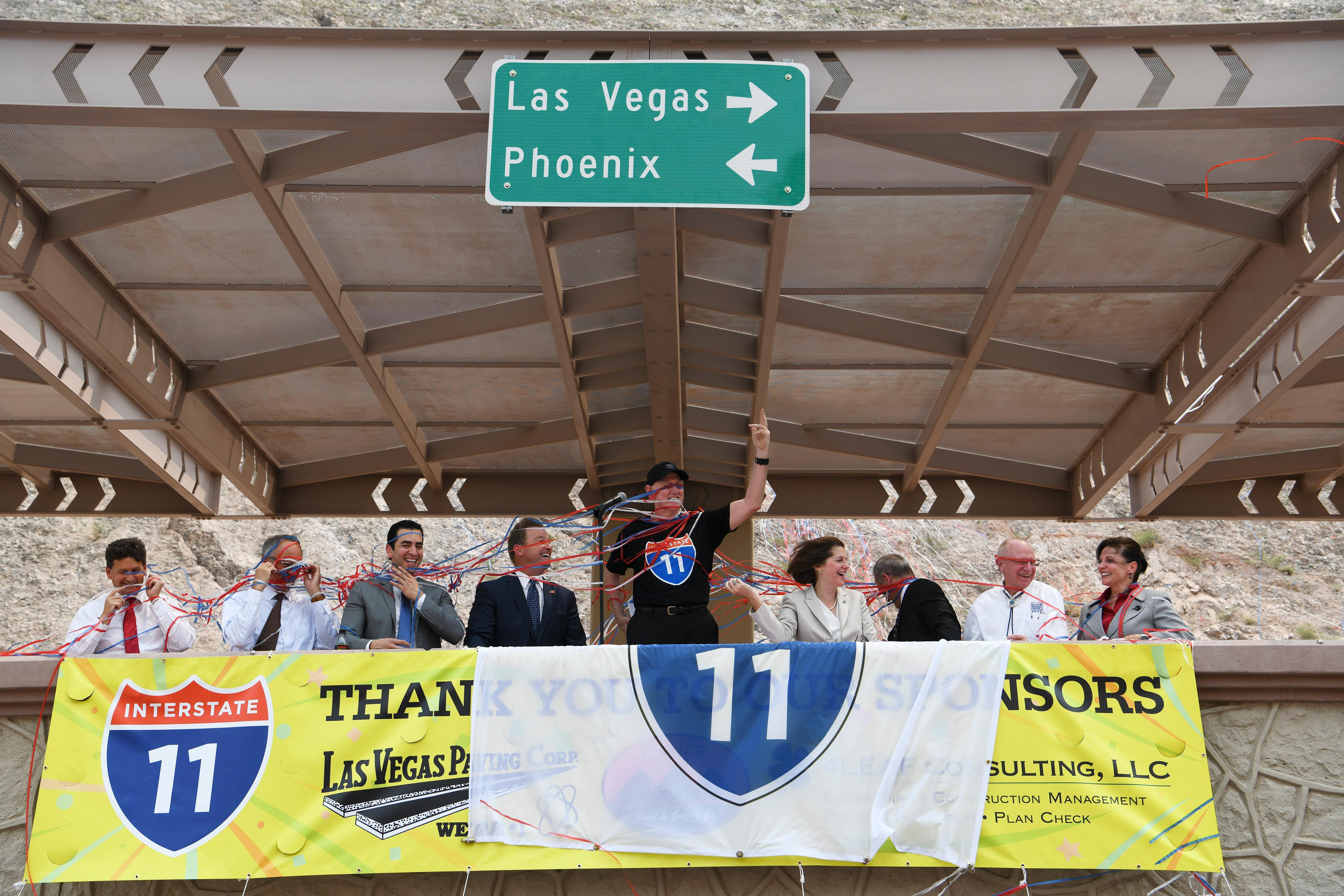 Elected officials and dignitaries get caught up in celebratory streamers during the grand opening of a new section of Interstate 11 Thursday, August 9, 2018, in Boulder City. From left are Boulder City Mayor Rod Woodbury, Clark County Commissioner Jim Gibson, Rep. Ruben Kihuen, D-Nev., Sen. Dean Heller, R-Nev., Clark County Commissioner Larry Brown, Sen. Catherine Cortez Masto, D-Nev., Federal Highway Administration Director of Field Services West Peter Osborn, Nevada State Sen. Joe Hardy, and Las Vegas Chamber of Commerce President Mary Beth Sewald. The section, also referred to as the Boulder City Bypass, marks the official start of the I-11 project between Las Vegas and Phoenix. CREDIT: Sam Morris/Las Vegas News Bureau