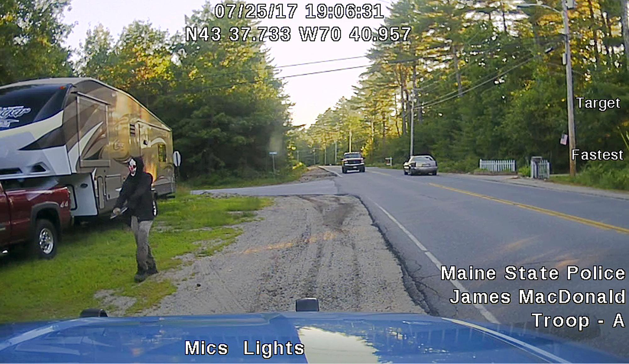 This Tuesday, July 25, 2017 patrol car dashboard camera image released by the Maine State Police shows a man strolling down a street in Hollis, Maine, who police said was wearing a clown mask with a machete taped to his amputated arm. Police said the man, Corey Berry, 31, of Hollis, was arrested and charged with criminal threatening. He was released after posting bail. (Maine State Police via AP)