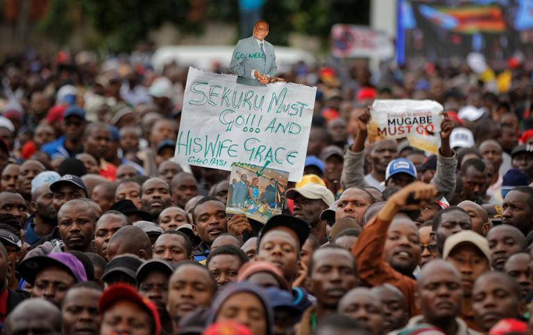 "A protester holds a banner referring to President Mugabe as ""grandfather"", at a demonstration at Zimbabwe Grounds in Harare, Zimbabwe Saturday, Nov. 18, 2017. Opponents of Mugabe are demonstrating for the ouster of the 93-year-old leader who is virtually powerless and deserted by most of his allies. (AP Photo/Ben Curtis)"
