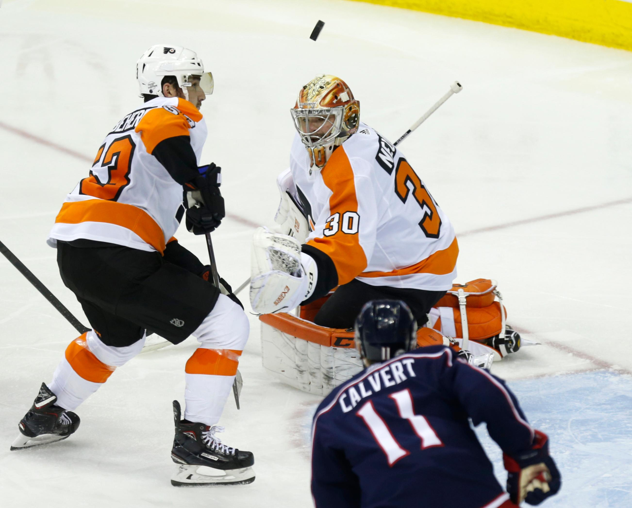 Philadelphia Flyers goalie Michal Neuvirth, top right, of the Czech Republic, stops a shot in front of Columbus Blue Jackets forward Matt Calvert (11) as Flyers defenseman Shayne Gostisbehere helps Neuvirth during the third period of an NHL hockey game in Columbus, Ohio, Friday, Feb. 16, 2018. The Flyers won 2-1 in overtime. (AP Photo/Paul Vernon)