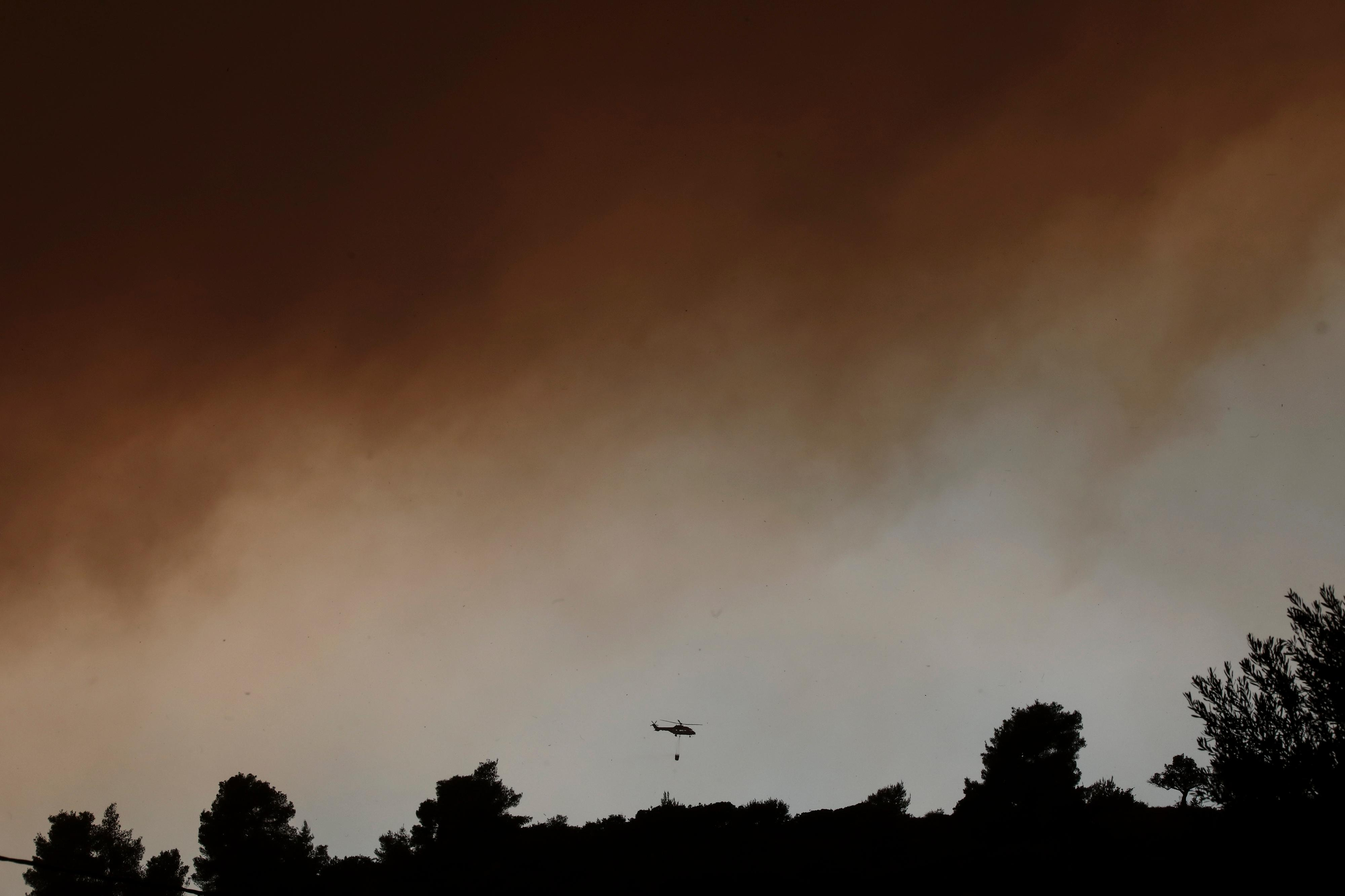 A firefighting helicopter flies below a thick cloud of smoke from a forest fire at Psachna village on the island of Evia, northeast of Athens, Tuesday, Aug. 13, 2019.{ } (AP Photo/Yorgos Karahalis)