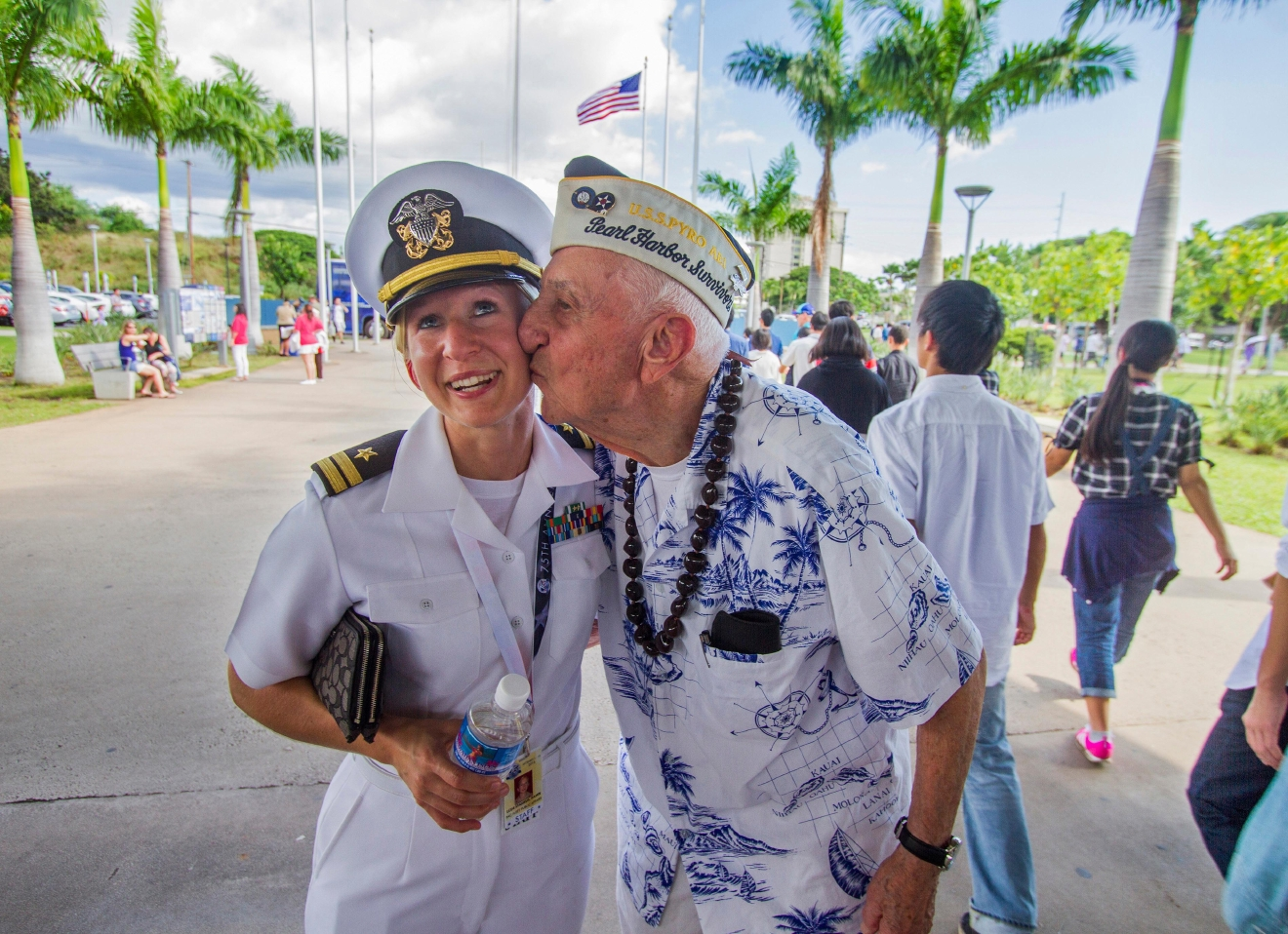 "In this Monday, Dec. 5, 2016 photo, about 30 Pearl Harbor Survivors with the ""Greatest Generation"" vets meet and greet with visitors at the Pearl Harbor Visitor Center in Honolulu. Lt. Dawn Stankus, left, was there to help escort the Pearl Harbor survivors and Edward W. Stone, right, suddenly gave her a kiss and said I hope you don't mind. Which Stankus said ""it was an honor to be kissed by you."" On Wednesday, Dec. 7, thousands of servicemen and women and members of the public are expected to attend the 75th anniversary ceremony of the attack on Pearl Harbor that left more than 2,300 service people dead.  (Dennis Oda/The Star-Advertiser via AP)"