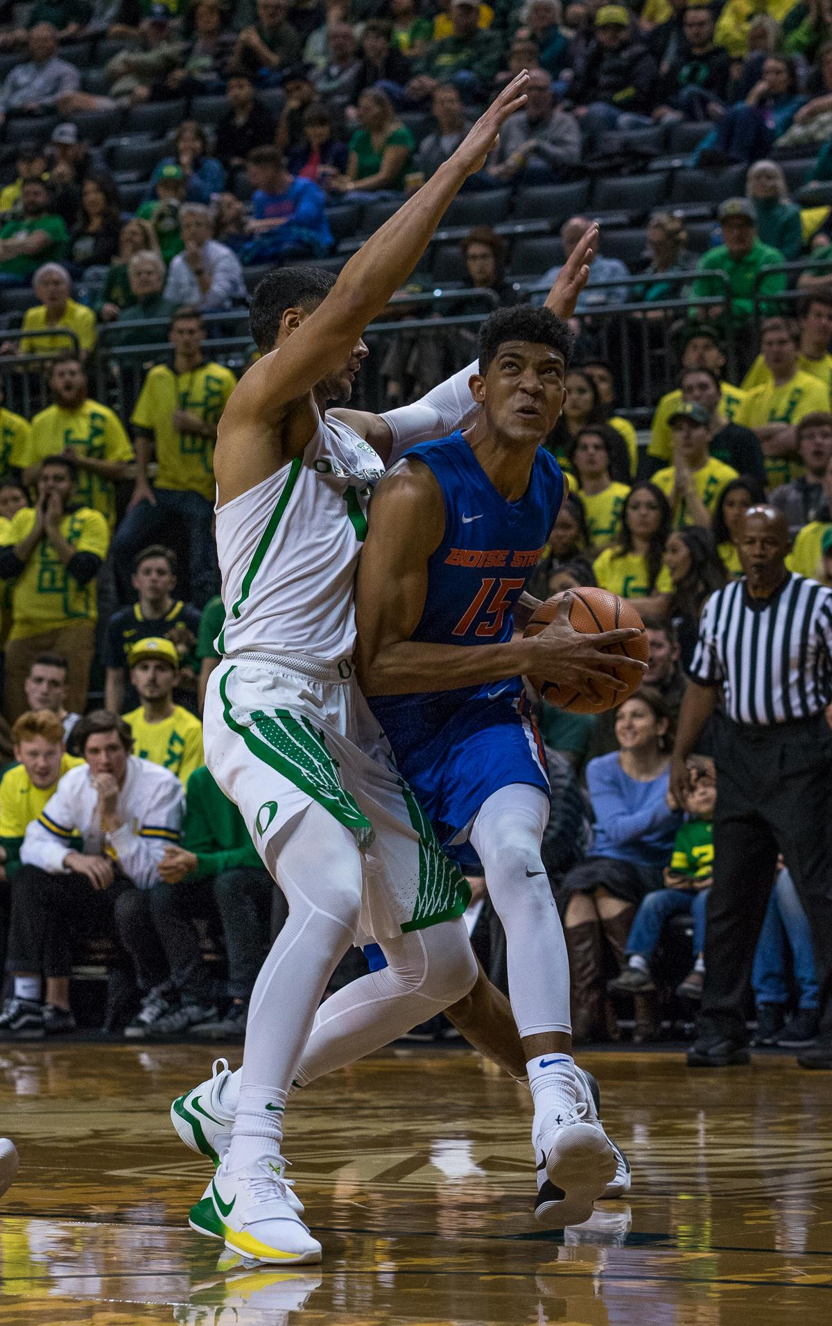 Boise State Bronco Chandler Hutchison (#15) rushes past Oregon Duck Keith Smith (#11). The Boise State Broncos defeated the University of Oregon Ducks 73 – 70 at Matthew Knight Arena in Eugene, Ore., on December 1, 2017. Photo by Kit MacAvoy, Oregon News Lab