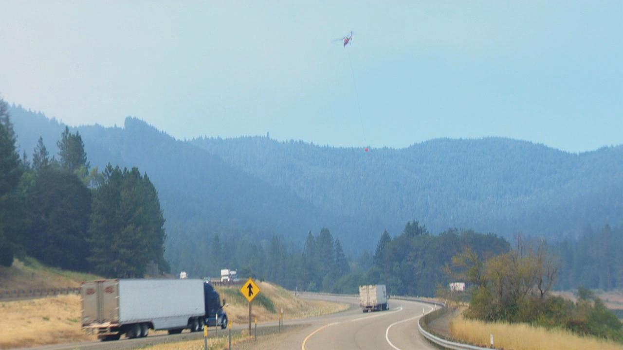 A helicopter flies over Interstate 5 Monday, July 29, 2019 toward the Milepost 97 fire to deliver water in the firefight. (KATU Photo)