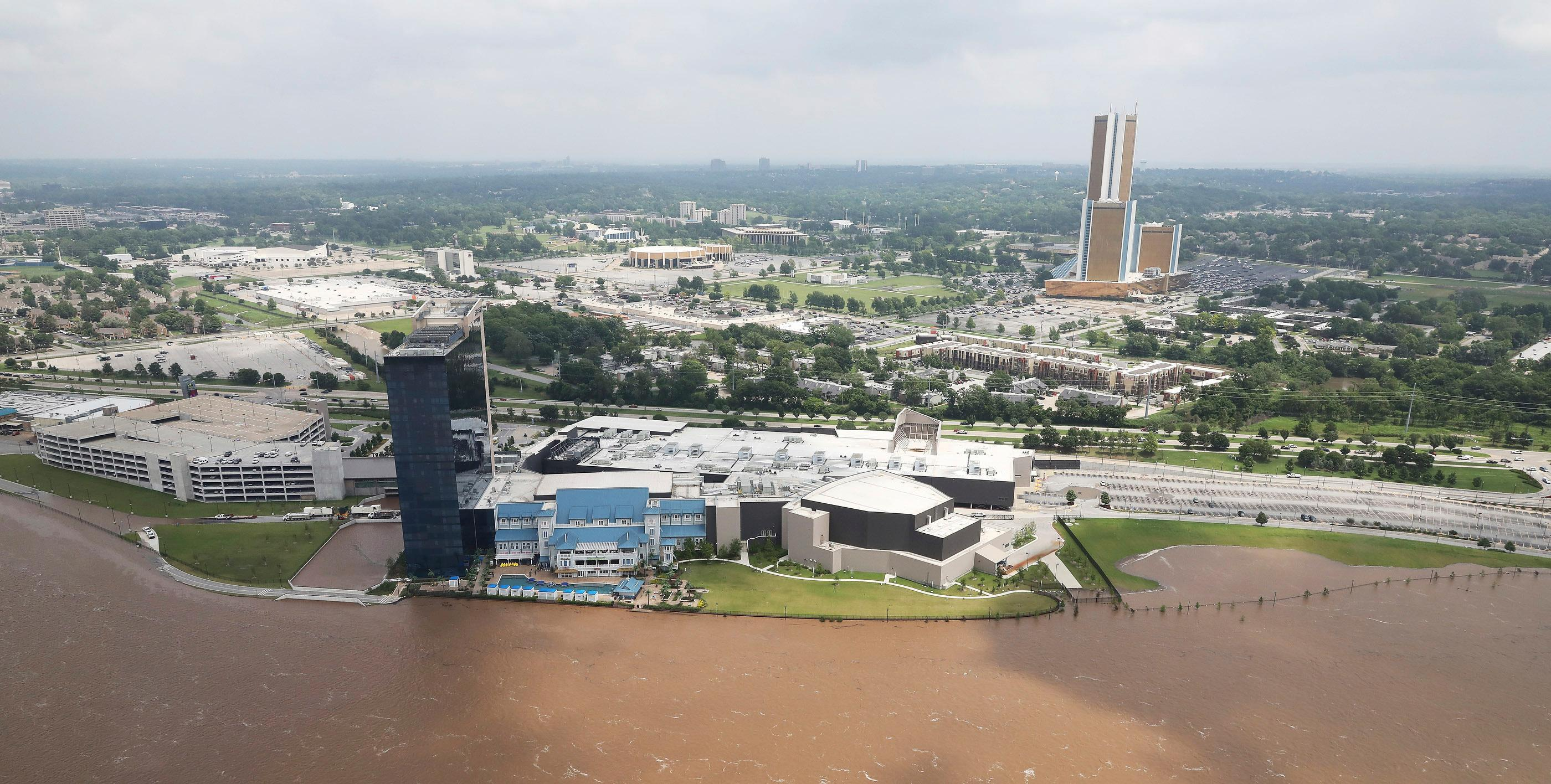 Flood waters encroach the River Spirit Hotel and Casino in Tulsa, Okla., on Wednesday, May 22, 2019. Authorities on Wednesday encouraged people living along the Arkansas River in the Tulsa suburb of Bixby and low-lying areas near creeks both north and south of Okmulgee, about 35 miles (56 kilometers) south of Tulsa. to leave their homes. (Tom Gilbert/Tulsa World via AP)