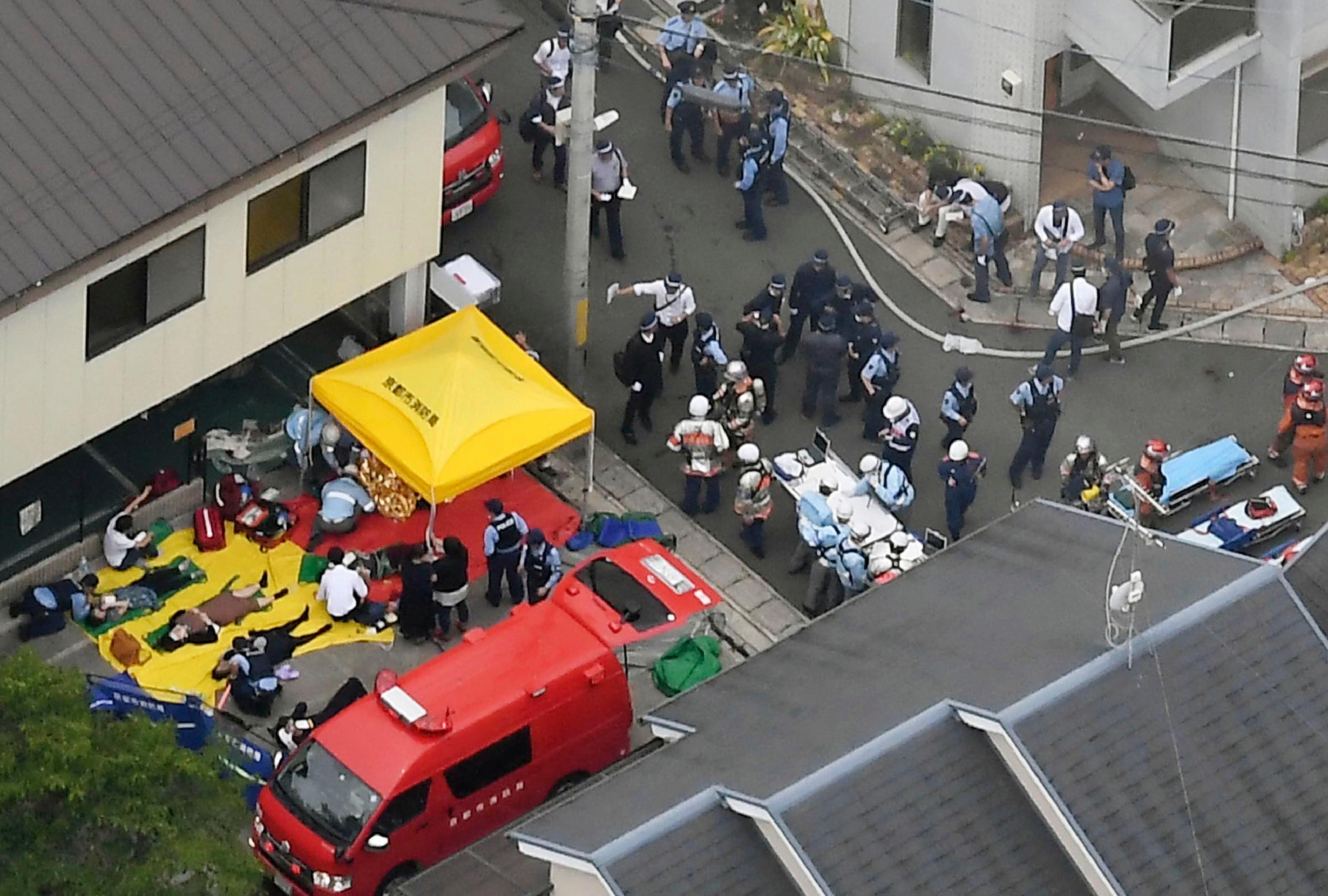 People injured in a fire are treated near a Kyoto Animation building in Kyoto, western Japan, Thursday, July 18, 2019. The fire broke out in the three-story building in Japan's ancient capital of Kyoto, after a suspect sprayed an unidentified liquid to accelerate the blaze, Kyoto prefectural police and fire department officials said.(Kyodo News via AP)