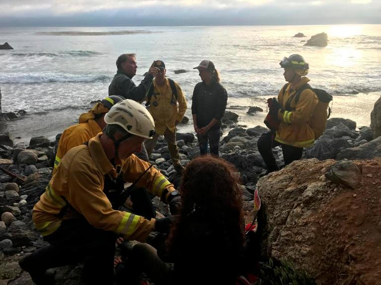 CORRECTS TO THE LOCATION TO BIG SUR, NOT MORRO BAY - In this Friday, July 13, 2018, photo posted on the Monterey County, Calif., Sheriff's Office Twitter feed, authorities tend to Angela Hernandez, foreground center, after she was rescued along Big Sur coastline, Calif. Authorities say a couple on a camping trip came upon Hernandez, from Oregon, who had been missing since July 6, after her car went over a cliff in coastal California. (Monterey County Sheriff's Office via AP)