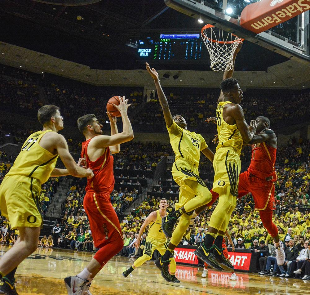 Wildcats Dusan Ristic (#14) guarded heavily on his way to the basket by Ducks forward Roman Sorkin (#41), Chris Boucher (#25) and Kavell Bigby-Williams (#35). In front of a sellout crowd the Ducks beat No. 5 Arizona 85-58, shooting a Mathew Knight Arena record 16 three-pointers, to clinch their 40th victory in a row at home. Photo by Jacob Smith, Oregon News Lab