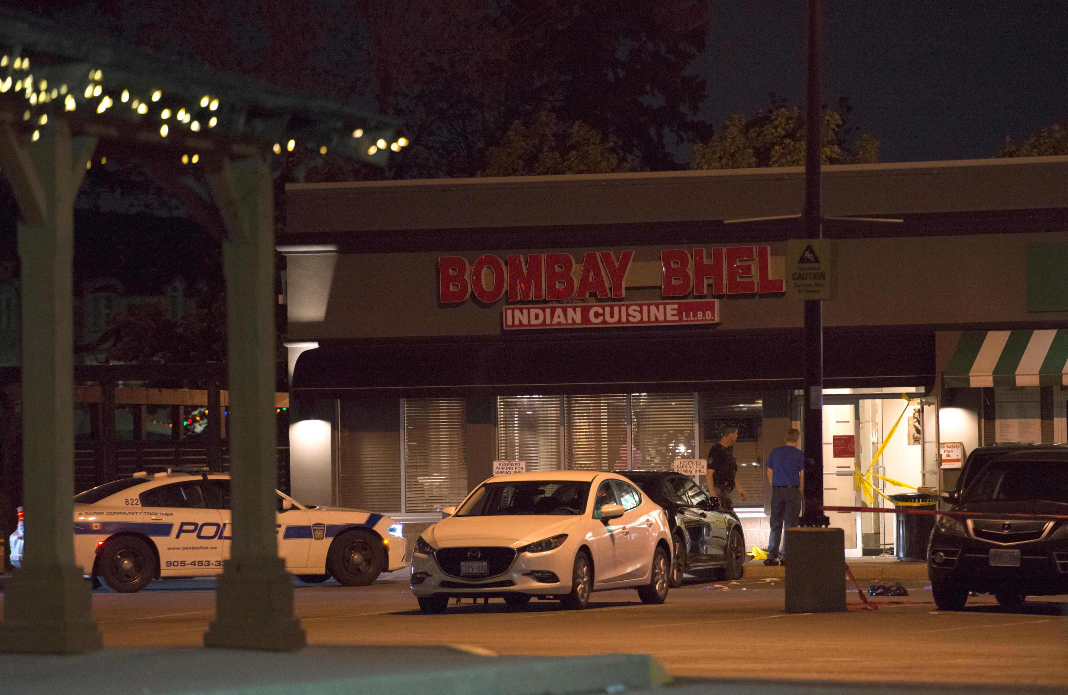 Police stand outside the Bombay Bhel restaurant in Mississauga, Canada Friday, May 25, 2018. Canadian police say an explosion set off deliberately in a restaurant has wounded a number of people. (Doug Ives/The Canadian Press via AP)