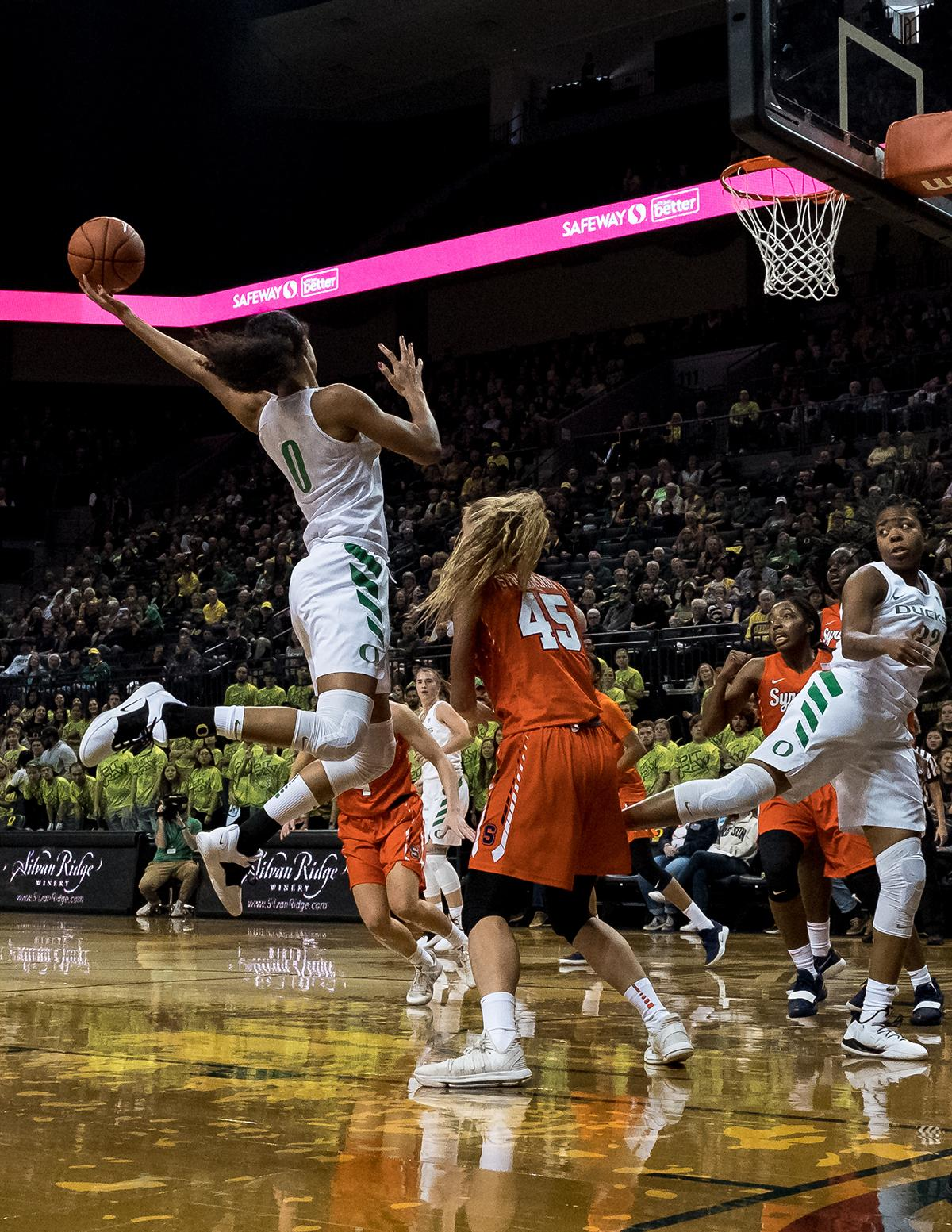 Oregon Ducks Satou Sabally (#0) stretches for an offensive rebound during Saturdays game against the Syracuse Orange. The 3rd ranked University of Oregon Ducks defeated 18th ranked Syracuse Orange 75-73 in a close game at Matthew Knight Arena Saturday. Sabrina Ionescu lead the Ducks with a double double, scoring 26 points and 10 rebounds. The Ducks Ruthy Hebard also finished the game with a double double, scoring 11 points and 14 rebounds. The Ducks had four players score in the double digits with Erin Boley scoring 13 and Maite Cazorla finishing the game with 14 points. In a tight game, the ducks lead the Orange 48-44 at the half. Syracuse took the lead with 3 minutes left in the game, but a 3-pointer by Ducks Erin Boley with 51 seconds left in the game would help the Ducks take the lead for the remainder. Oregon is now 2-0 on the season. The Ducks travel to Utah State Wednesday November 14th before returning to Matthew Knight Arena Sunday November 18th to face Buffalo. Photo by Jeff Dean