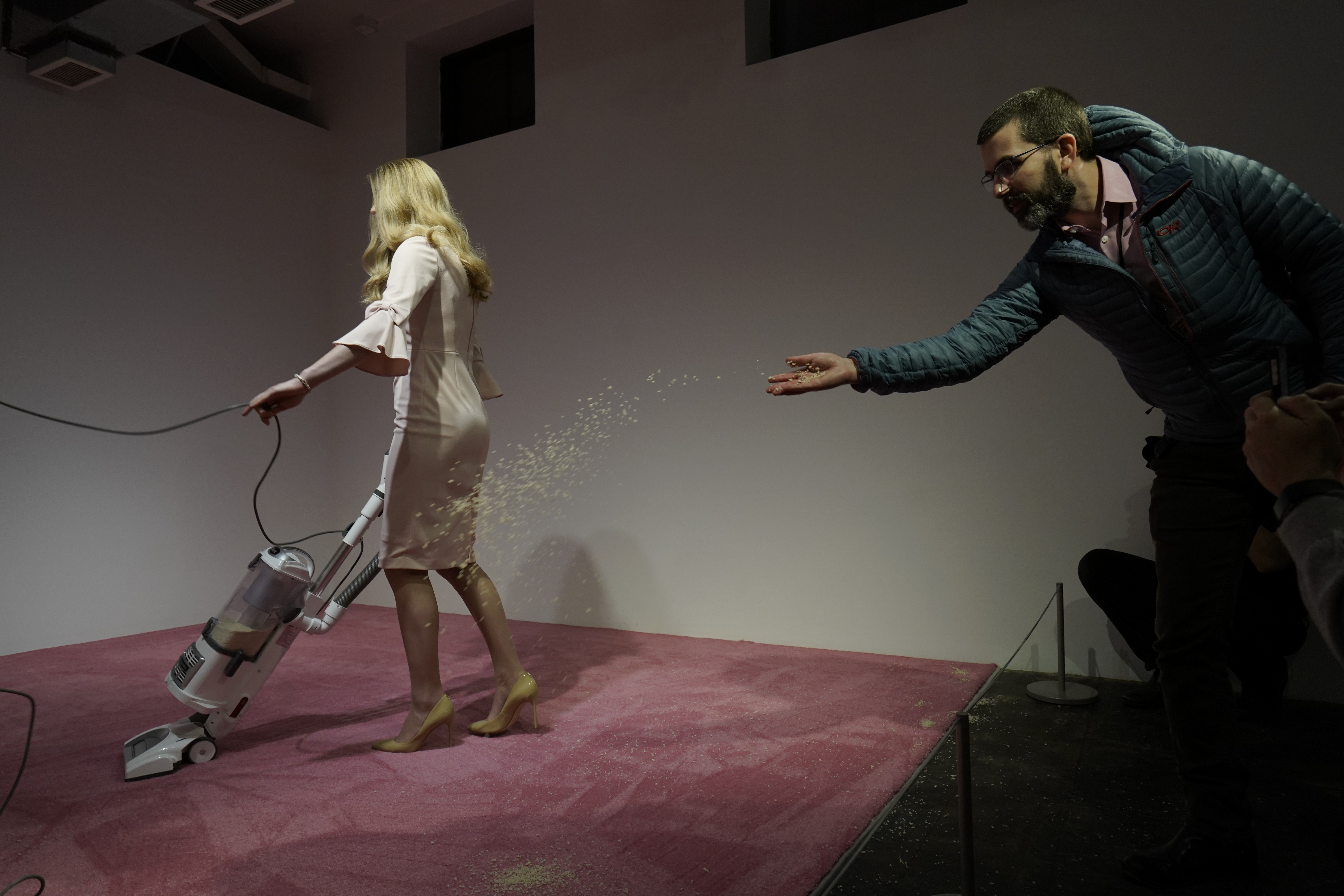 "A spectator tosses crumbs for an Ivanka Trump lookalike to vacuum at Jennifer Rubell's art exhibit ""Ivanka Vacuuming 2019"" on Tuesday, Feb. 5, 2019, at Flashpoint Gallery in Washington. (AP Photo/Sait Serkan Gurbuz)"