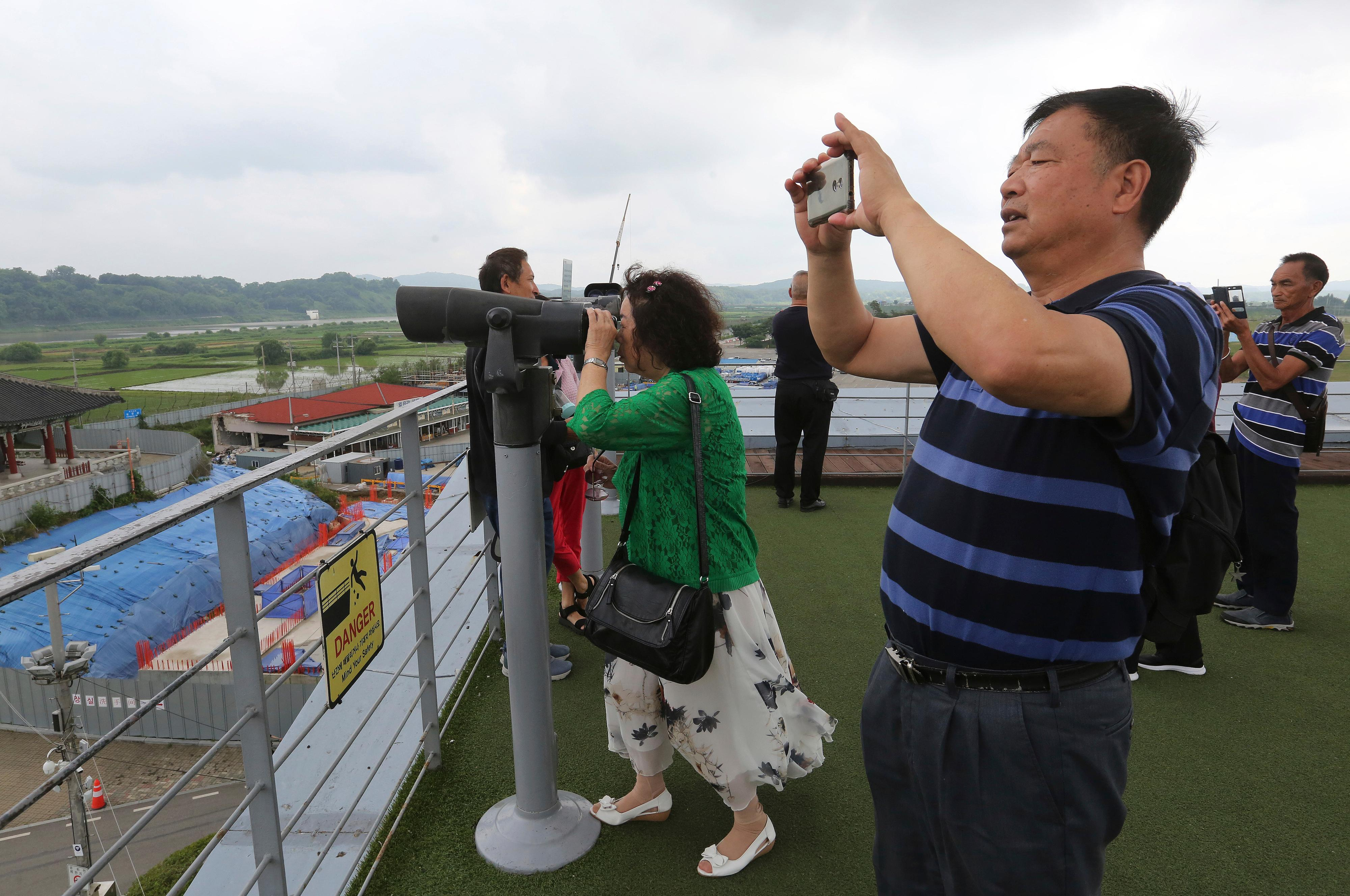 Chinese visitors look toward the North's side at the Imjingak Pavilion, near the demilitarized zone of Panmunjom, in Paju, South Korea, Thursday, June 20, 2019. (AP Photo/Ahn Young-joon)