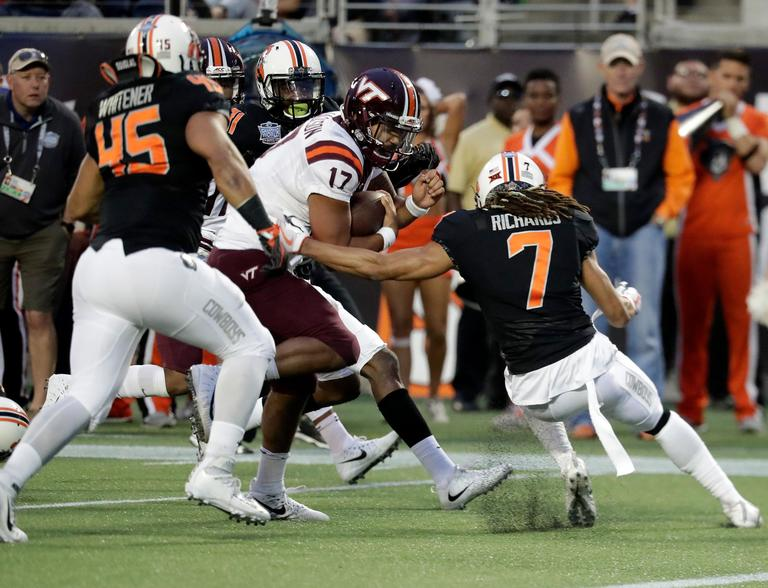 Virginia Tech quarterback Josh Jackson (17) runs past Oklahoma State linebacker Chad Whitener (45) and safety Ramon Richards (7) for a 13-yard touchdown during the first half of the Camping World Bowl NCAA college football game Thursday, Dec. 28, 2017, in Orlando, Fla. (AP Photo/John Raoux)