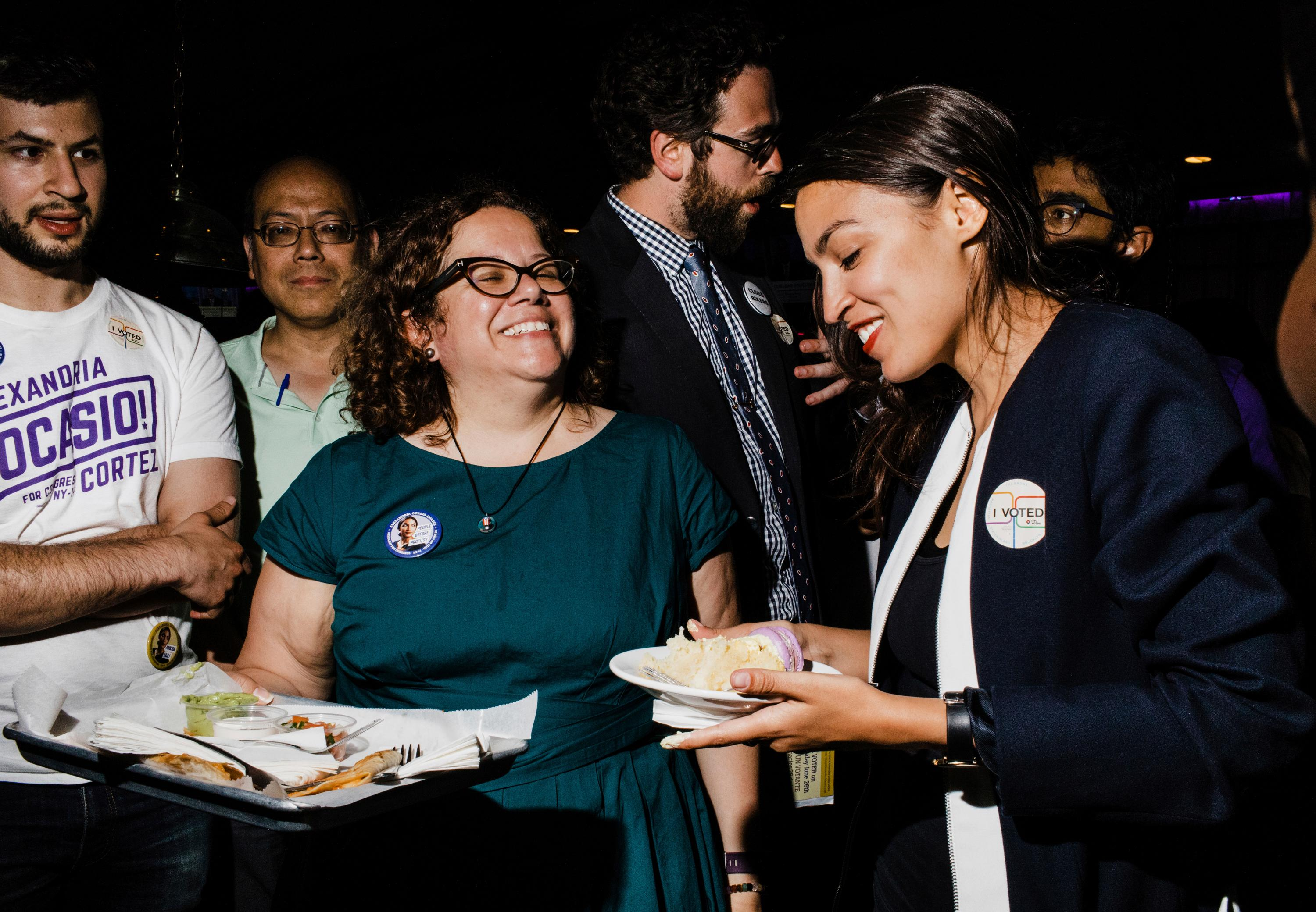 In this June 27, 2018 photo provided by Ocasio2018, Alexandria Ocasio-Cortez, right, 28, celebrates her Democratic congressional primary victory over 10-term incumbent Joe Crowley with campaign manager Virginia Ramos Rios, center left, and campaign staffer Daniel Bonthius, fourth from left, during an election night party at a pool hall in the Bronx borough of New York. Ramos Rios and Bonthius were part of a eclectic team that came together to help their candidate defeat an incumbent who spent  $3.4 million on his campaign. (Ocasio2018/Corey Torpie via AP)