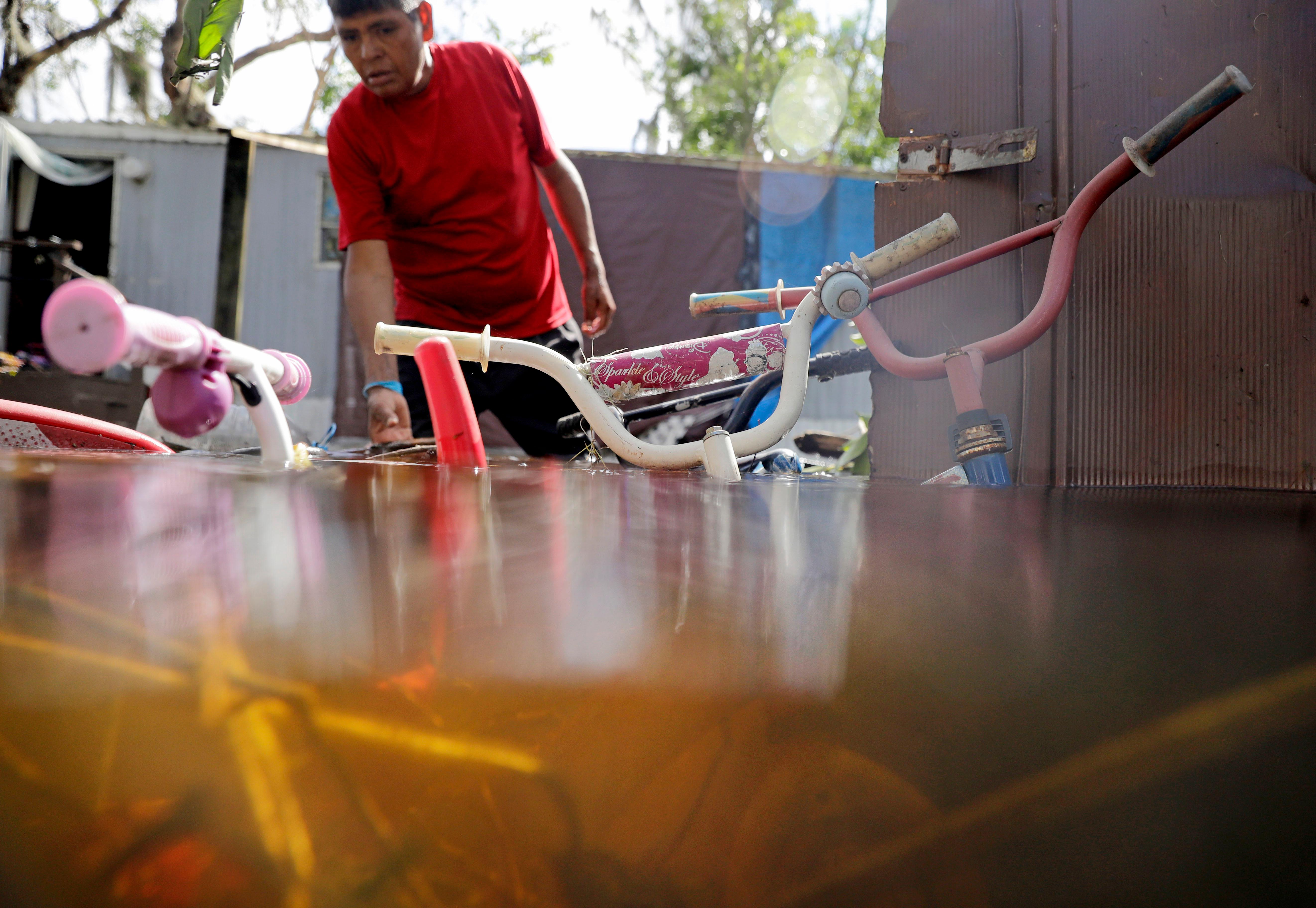Children's bicycles are flooded outside a home as Ezequiel Cruz retrieves belongings in the aftermath of Hurricane Irma in Bonita Springs, Fla., Tuesday, Sept. 12, 2017. (AP Photo/David Goldman)