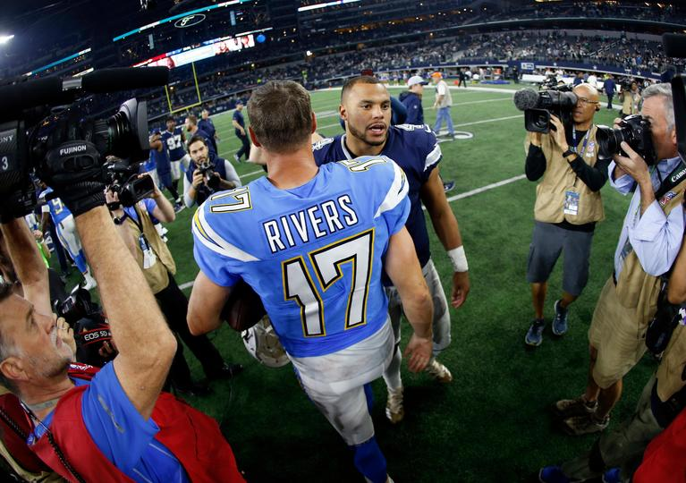 Los Angeles Chargers' Philip Rivers (17) and Dallas Cowboys' Dak Prescott, center rear, greet each other at midfield after after an NFL football game, Thursday, Nov. 23, 2017, in Arlington, Texas. (AP Photo/Ron Jenkins)