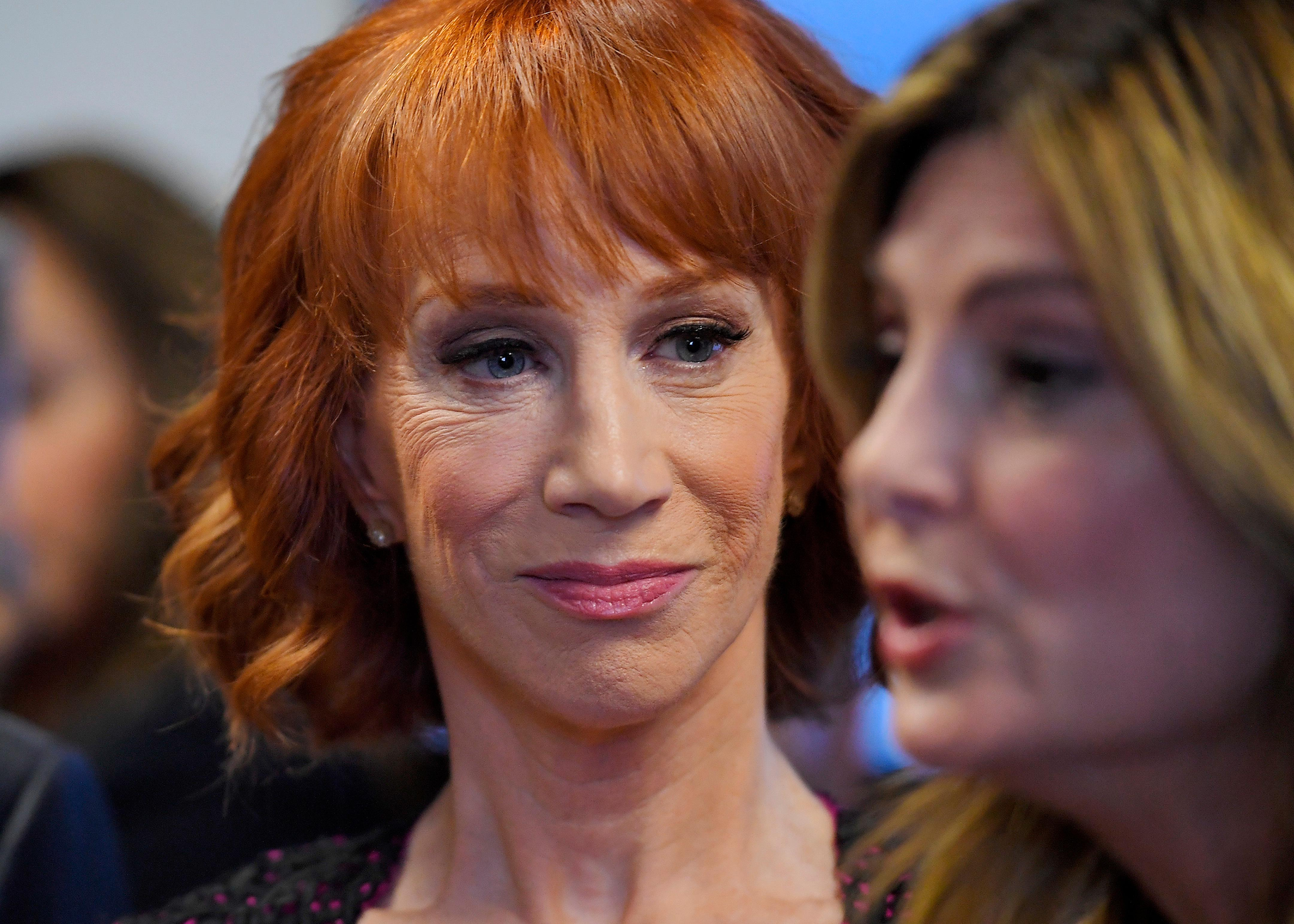FILE - In this June 2, 2017, file photo, comedian Kathy Griffin, left, listens as her attorney Lisa Bloom speaks during a news conference in Los Angeles, to discuss the backlash since Griffin released a photo and video of her displaying a likeness of President Donald Trump's severed head. The AP reported on July 28, 2017, that a story claiming Griffin was jailed last month for walking around New York wearing fake blood and a Trump Halloween mask is a hoax. (AP Photo/Mark J. Terrill, File)