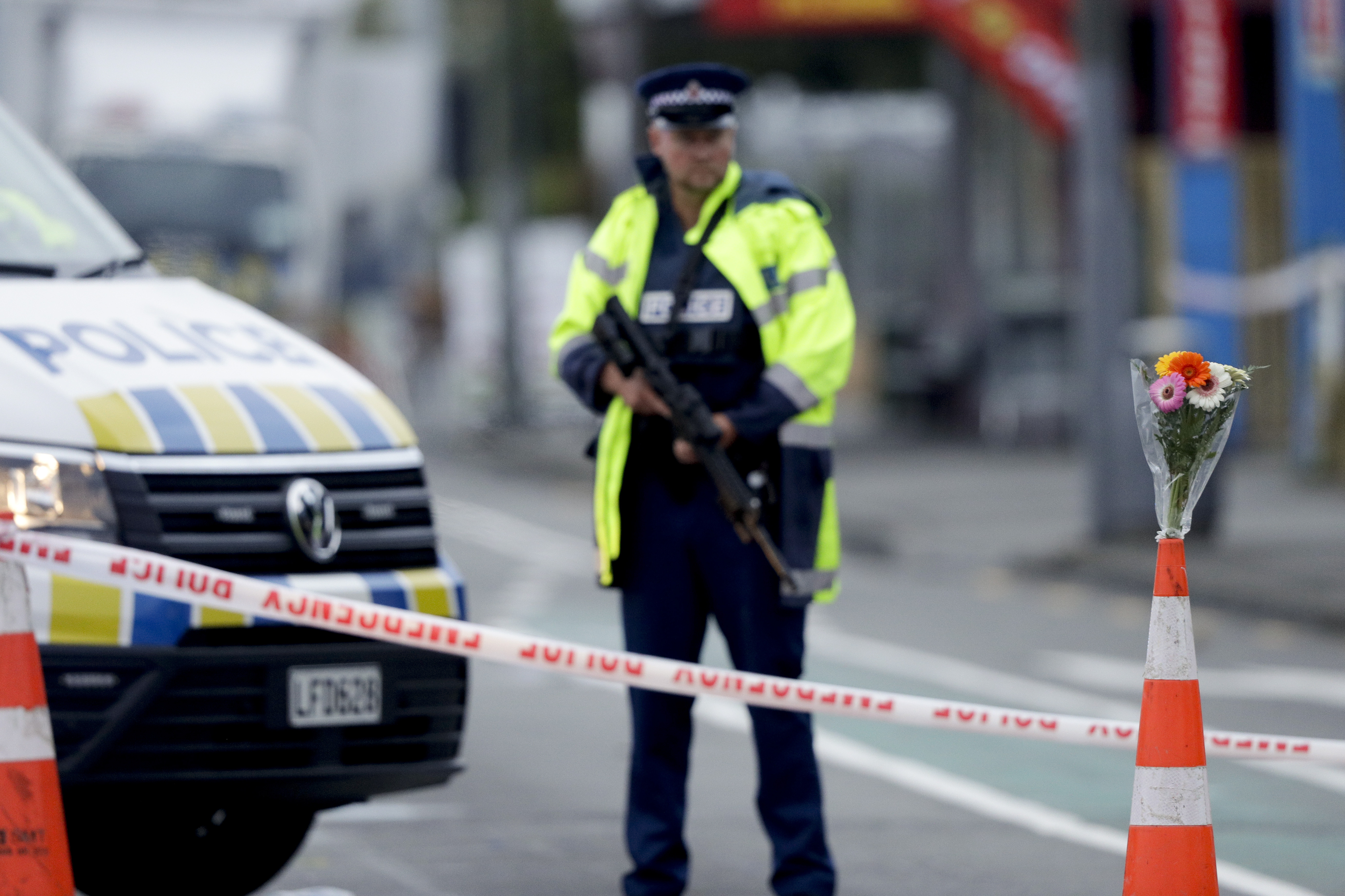 Flower rest at a road block, as a Police officer stands guard near the Linwood mosque, site of one of the mass shootings at two mosques in Christchurch, New Zealand, Saturday, March 16, 2019. (AP Photo/Mark Baker)