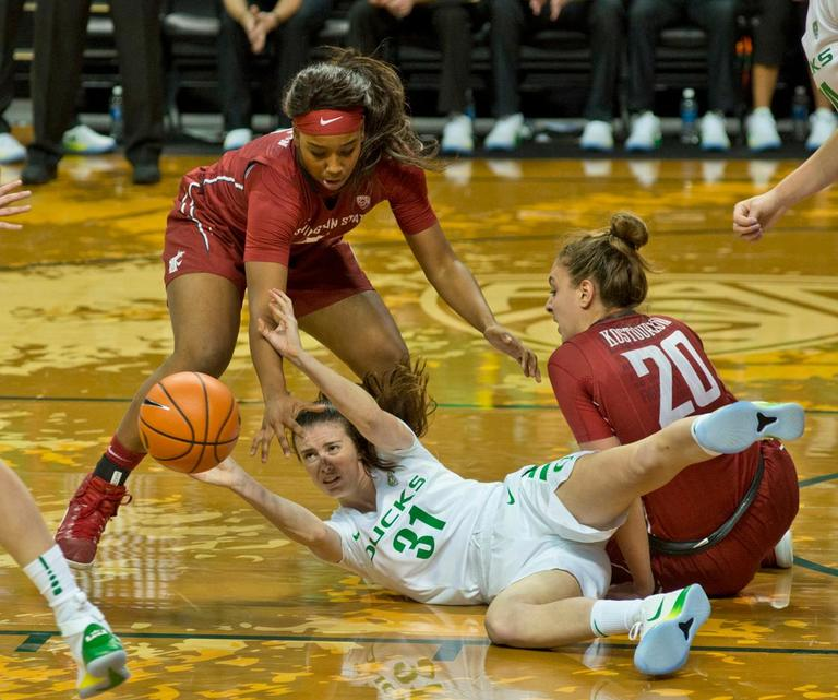 University of Oregon Ducks Aina Ayuso (#31) fights for control of the ball with Washington State University Cougars Kayla Washington (#5, standing left) and Maria Kostourkova (#20). In their first conference basketball game of the season, the Oregon Women Ducks defeated the Washington State University Cougars 89-56 in Matt Knight Arena Saturday afternoon. Oregon's Ruthy Hebard ran up 25 points with 10 rebounds. Sabrina Ionescu shot 25 points with five three-pointers and three rebounds. Lexi Bando added 18 points, with four three-pointers and pulled down three rebounds. Satou Sabally ended the game with 14 points with one three-pointer and two rebounds. The Ducks are now 12-2 overall with 1-0 in conference and the Cougars stand at 7-6 overall and 0-1 in conference play. The Oregon Women Ducks next play the University of Washington Huskies at 1:00 pm on Sunday. Photo by Dan Morrison, Oregon News Lab