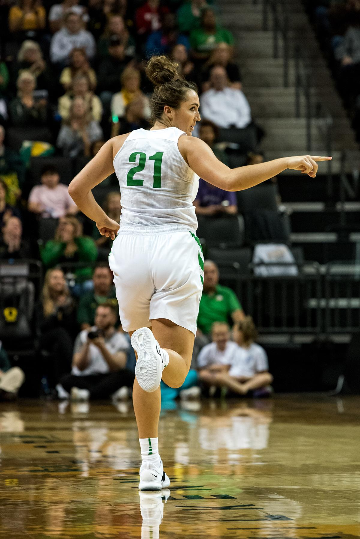 Oregon Ducks Erin Boley (#21) points to teammates after scoring during Saturdays game against Syracuse. The 3rd ranked University of Oregon Ducks defeated 18th ranked Syracuse Orange 75-73 in a close game at Matthew Knight Arena Saturday. Sabrina Ionescu lead the Ducks with a double double, scoring 26 points and 10 rebounds. The Ducks Ruthy Hebard also finished the game with a double double, scoring 11 points and 14 rebounds. The Ducks had four players score in the double digits with Erin Boley scoring 13 and Maite Cazorla finishing the game with 14 points. In a tight game, the ducks lead the Orange 48-44 at the half. Syracuse took the lead with 3 minutes left in the game, but a 3-pointer by Ducks Erin Boley with 51 seconds left in the game would help the Ducks take the lead for the remainder. Oregon is now 2-0 on the season. The Ducks travel to Utah State Wednesday November 14th before returning to Matthew Knight Arena Sunday November 18th to face Buffalo. Photo by Jeff Dean