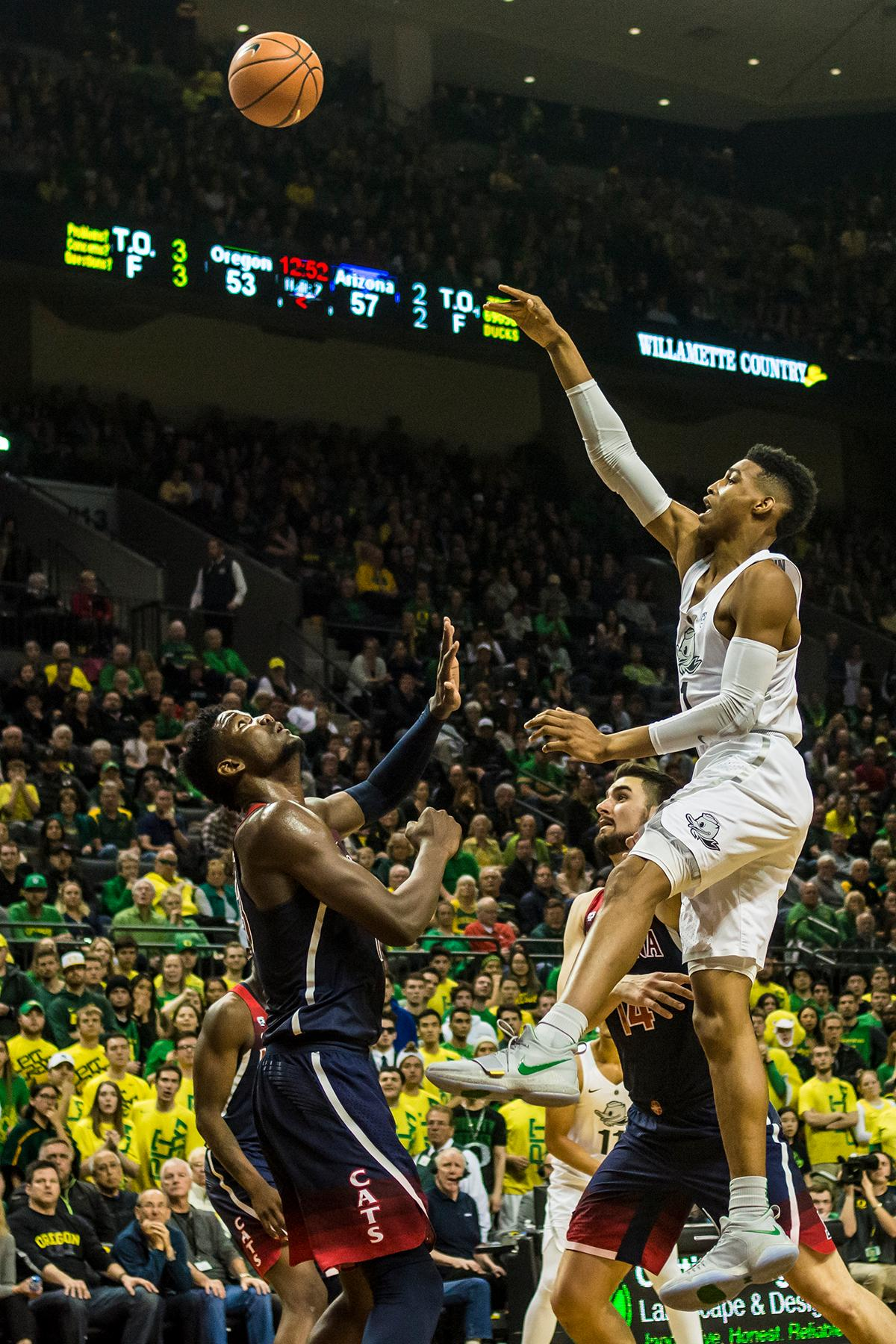 Oregon's Kenny Wooten (1) shoots over Arizona's DeAndre Ayton in their matchup at Matthew Knight Arena Saturday. The Ducks upset the fourteenth ranked Wildcats 98-93 in a stunning overtime win in front of a packed house of over 12,000 fans for their final home game to improve to a 19-10 (9-7 PAC-12) record on the season. Oregon will finish out regular season play on the road in Washington next week against Washington State on Thursday, then Washington on the following Saturday. (Photo by Colin Houck)