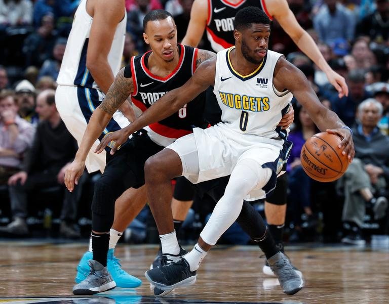 Portland Trail Blazers guard Shabazz Napier, left, fouls Denver Nuggets guard Emmanuel Mudiay in the second half of an NBA basketball game Monday, Jan. 22, 2018, in Denver. The Nuggets 104-101. (AP Photo/David Zalubowski)