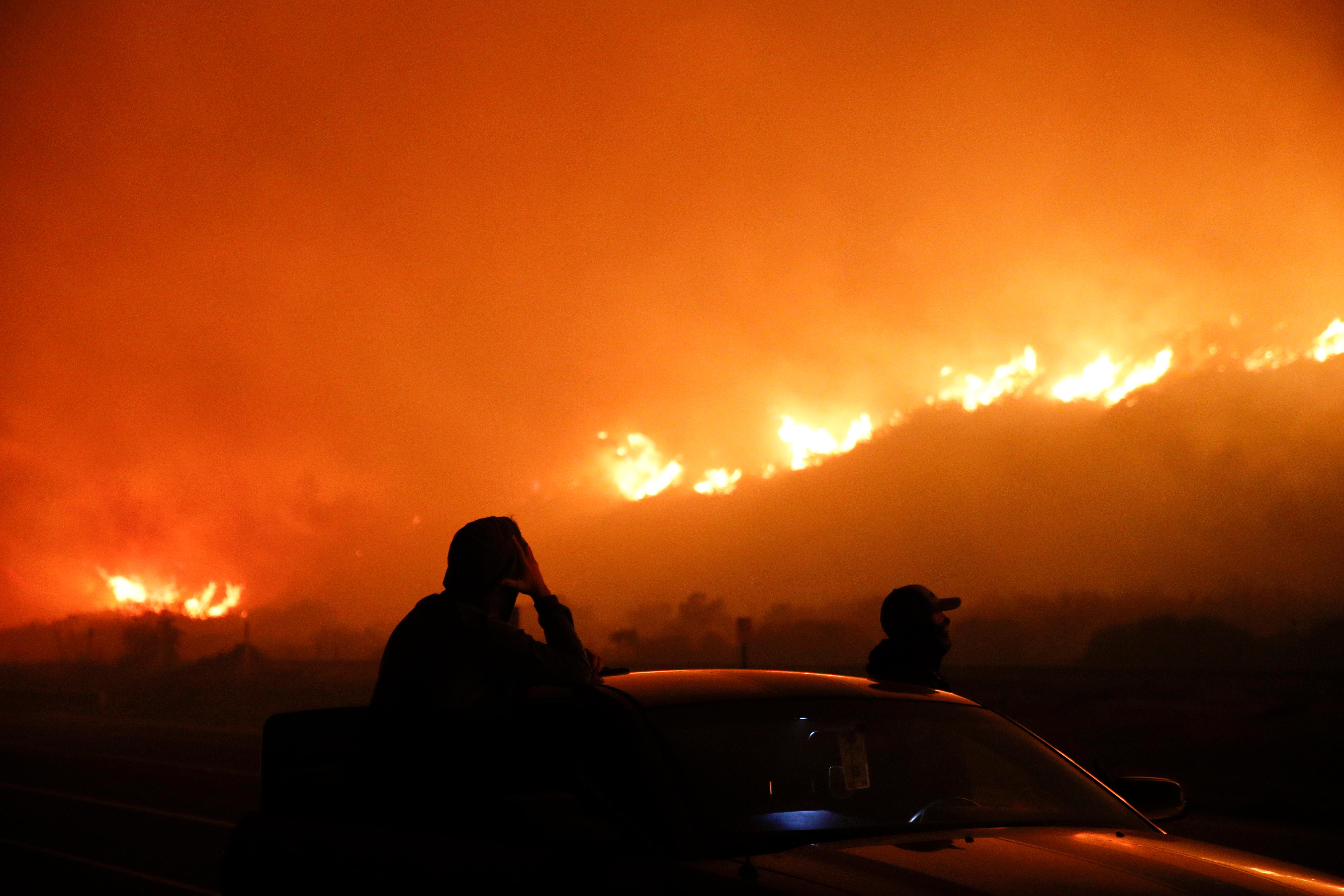Two spectators watch as a wildfire burns along the 101 Freeway Tuesday, Dec. 5, 2017, in Ventura, Calif. Raked by ferocious Santa Ana winds, explosive wildfires northwest of Los Angeles and in the city's foothills burned a psychiatric hospital and scores of homes and other structures Tuesday and forced the evacuation of tens of thousands of people. (AP Photo/Jae C. Hong)
