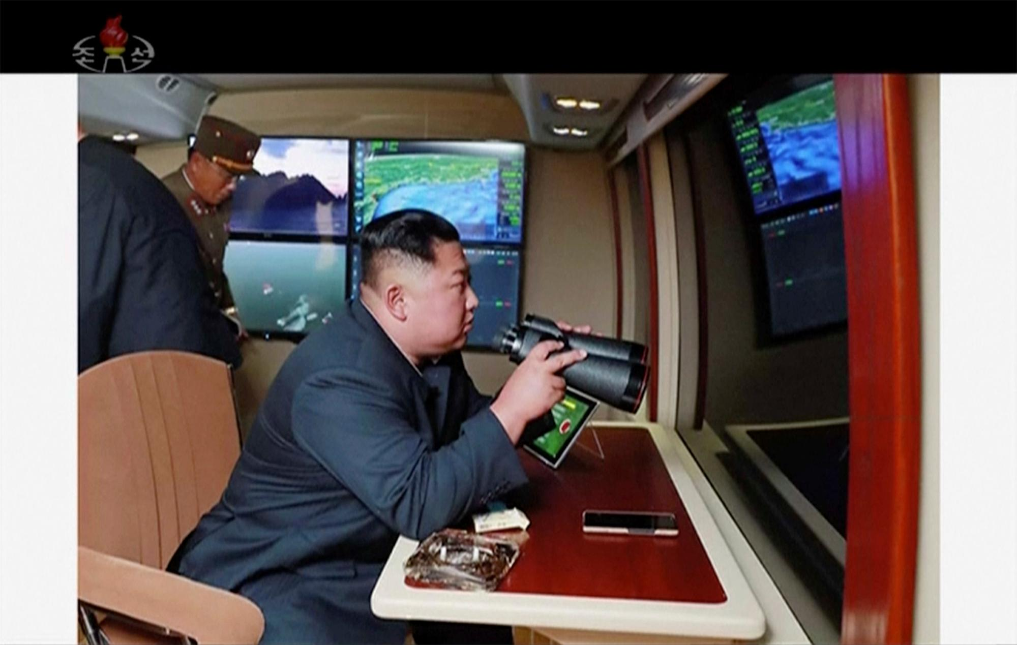 In this image made from video of a still image broadcasted by North Korea's KRT on Thursday, Aug. 1, 2019, North Korean leader Kim Jong Un, equipped with binoculars, supervises a rocket launch test. (KRT via AP Video)